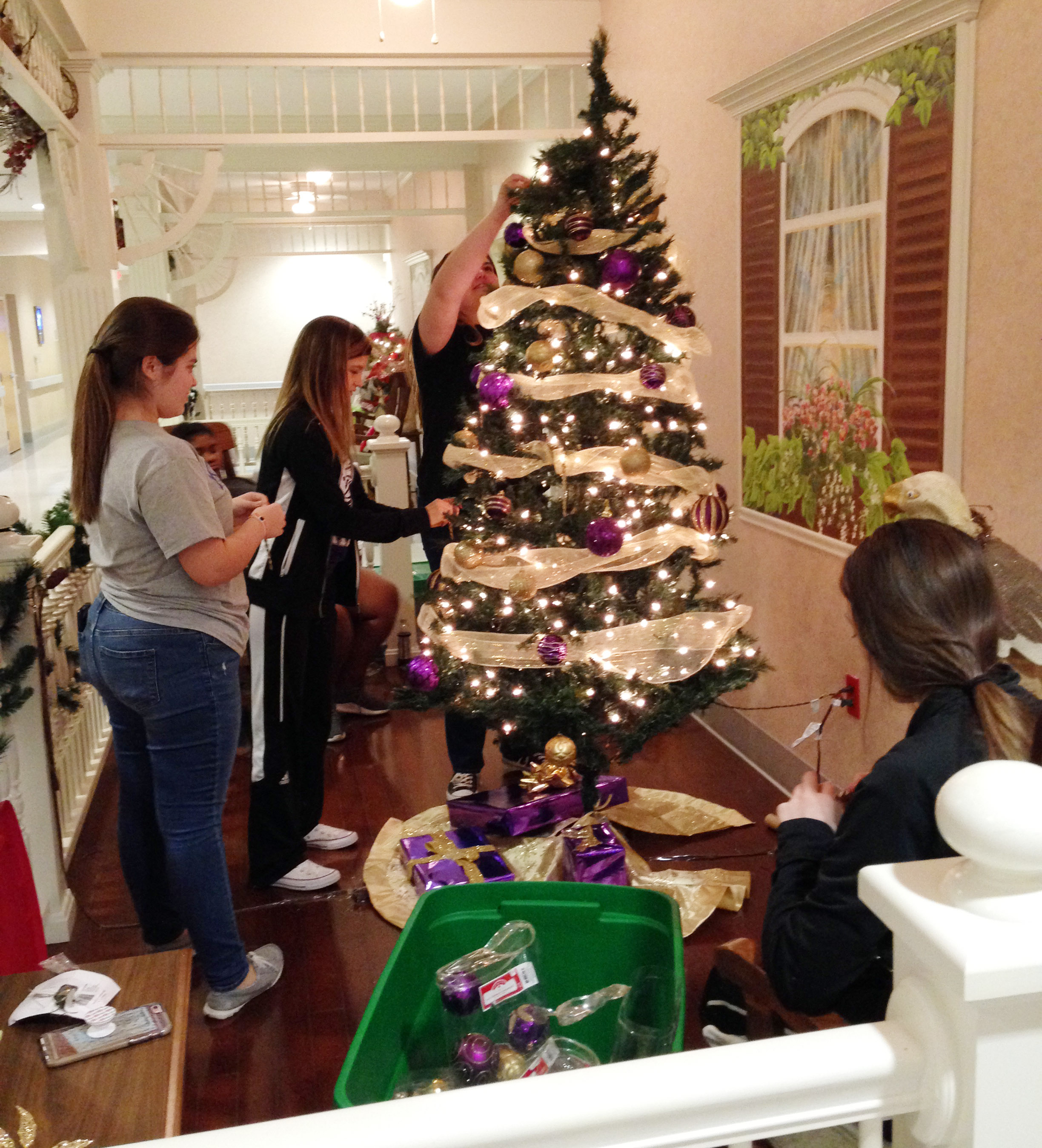 From left, CHS freshmen Chloe Garrett and Carly Adams, senior Vivian Brown and junior Caleigh Bright decorate the FCCLA club's Christmas tree, which is on display at the Grandview.