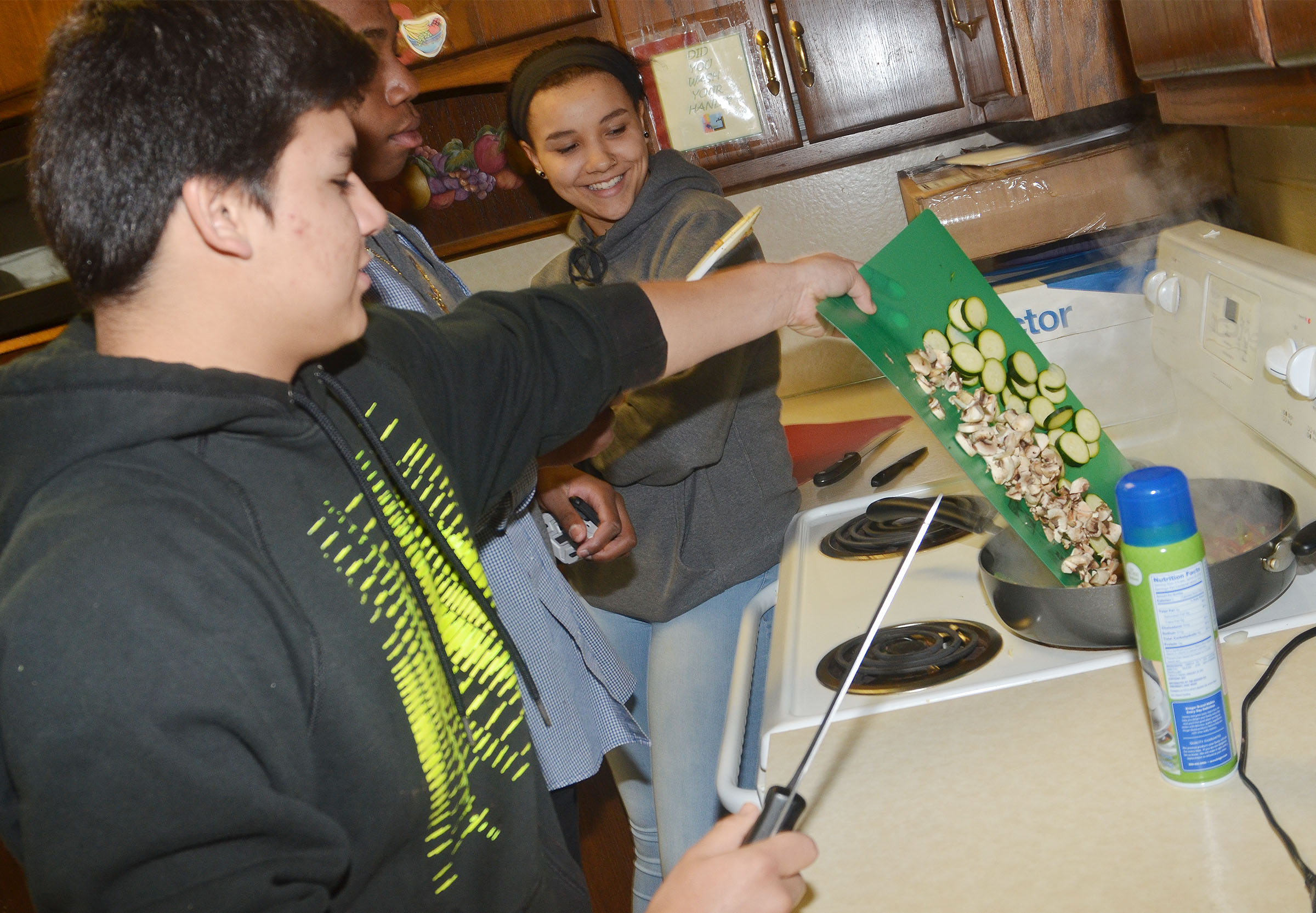 CHS freshman Greg Lopez adds mushrooms and zucchini to the class's stir fry.