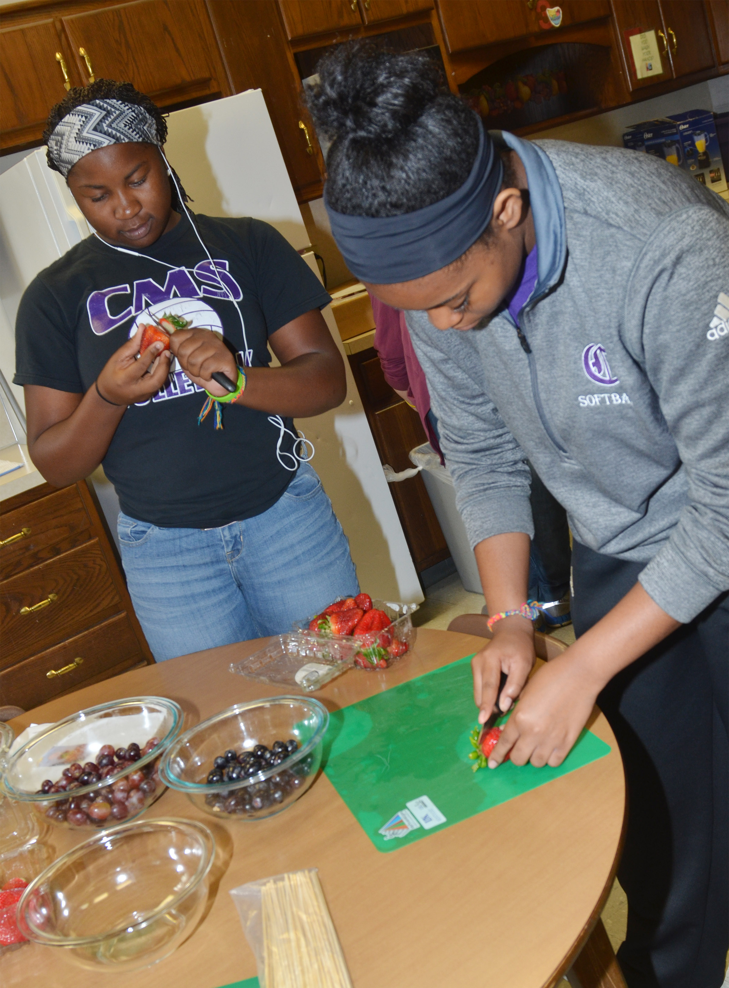 CHS juniors Kiyah Barnett, at left, and Vonnea Smith prepare fruit for the fruit arrangement they will make with their classmates.