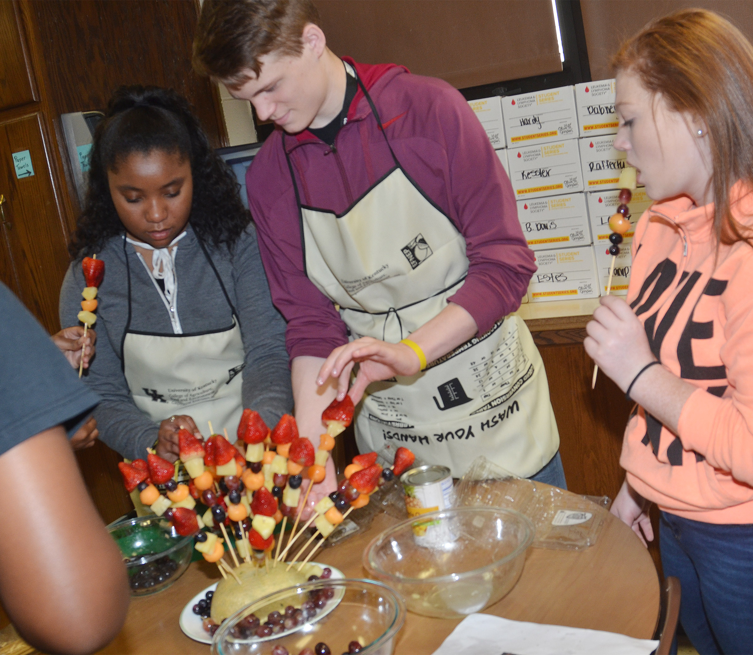 CHS senior Kayla Atkinson and sophomore Joe Pipes work together to make a fruit arrangement, at left, while sophomore Bethany Harris enjoys some fruit.