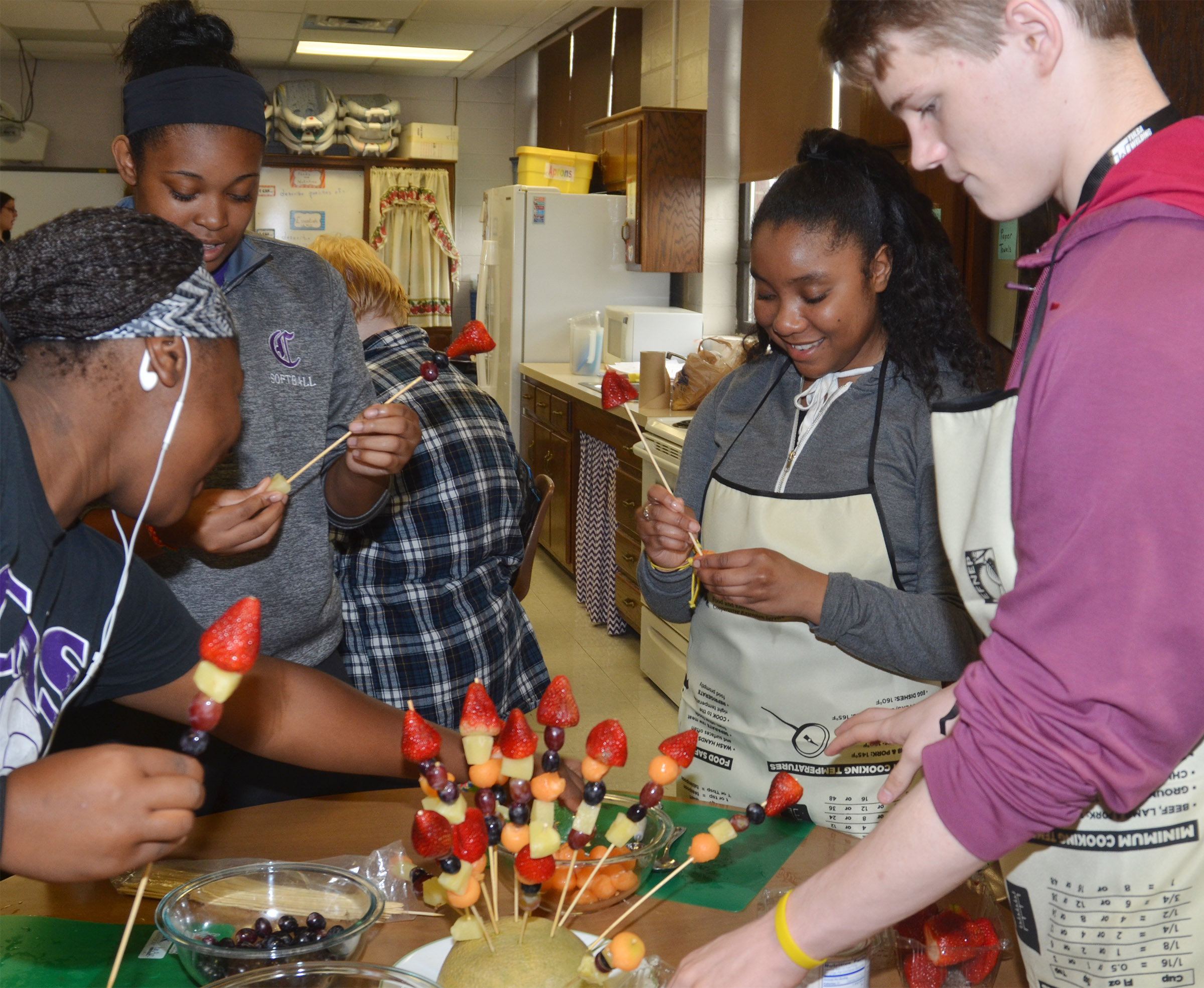 From left, CHS juniors Kiyah Barnett and Vonnea Smith, senior Kayla Atkinson and sophomore Joe Pipes make a fruit arrangement.