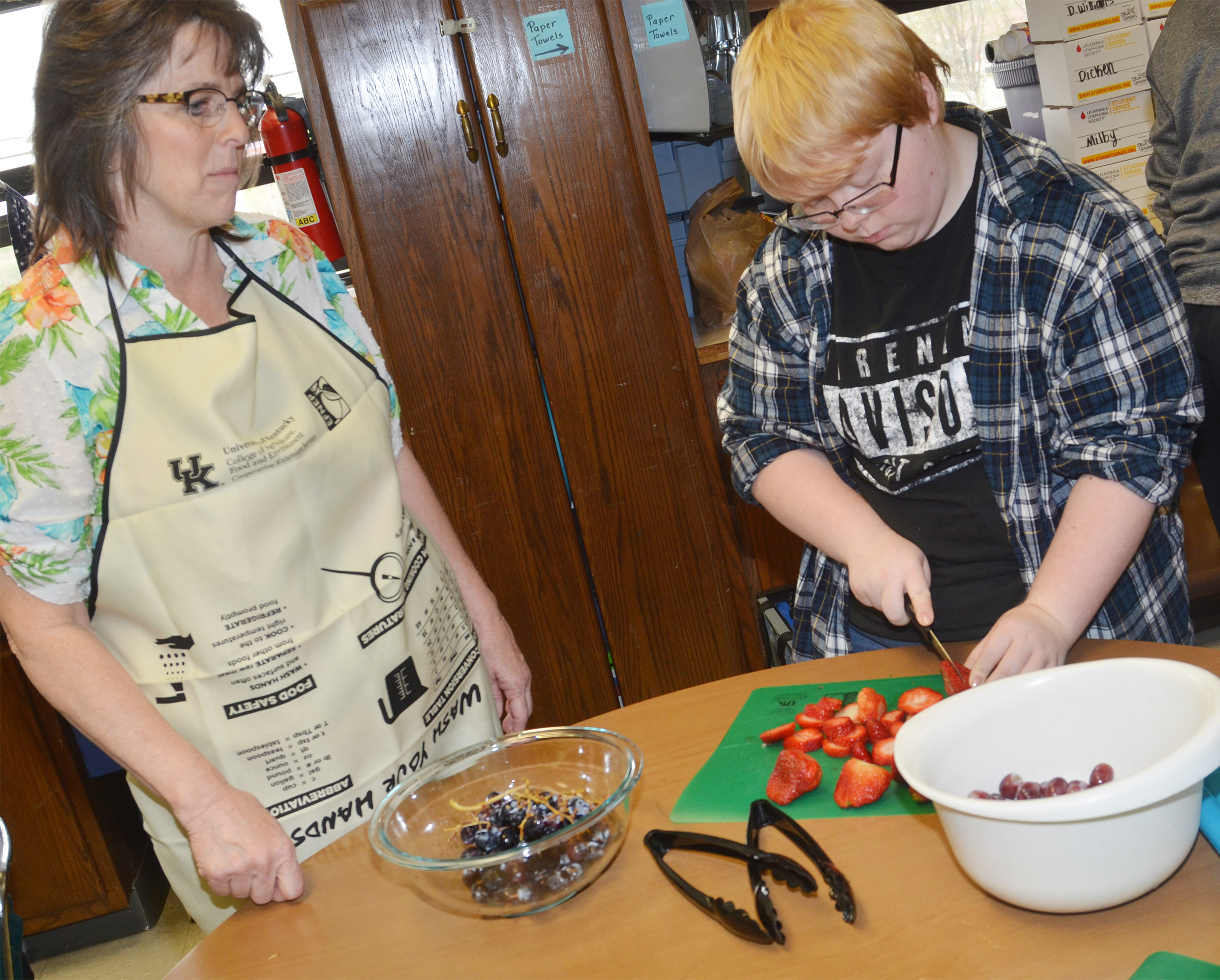 CHS teacher Deanna Campbell helps sophomore Jessie Bennett cut fruit.