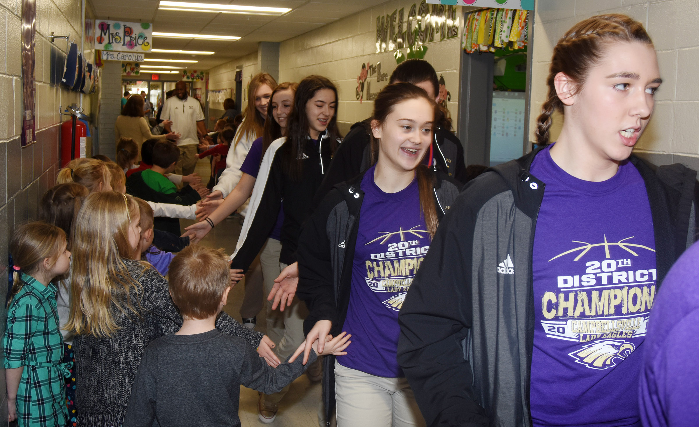 CHS girls' basketball players high-five CES students.