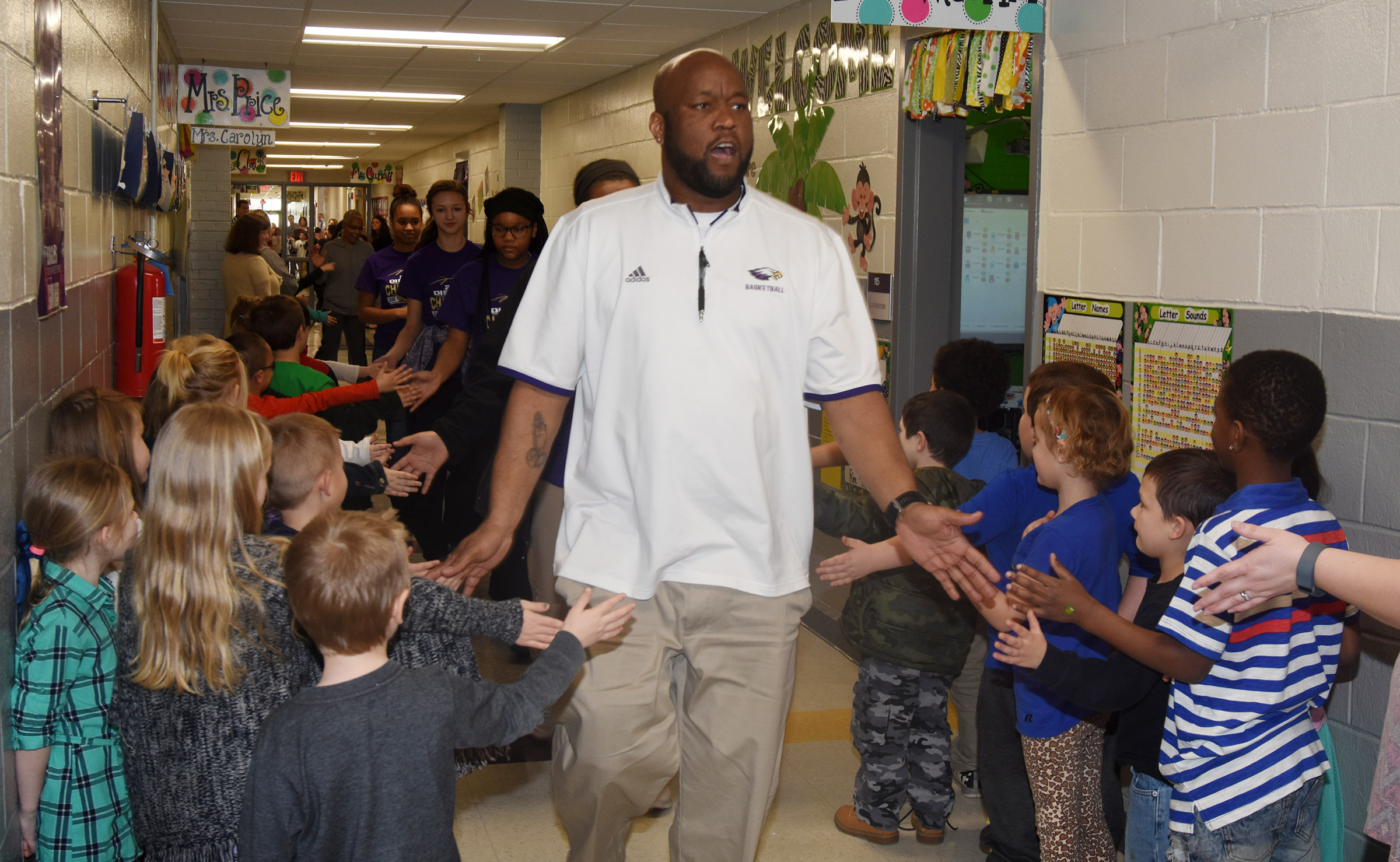 CHS girls' basketball head coach Anthony Epps high-fives CES students.