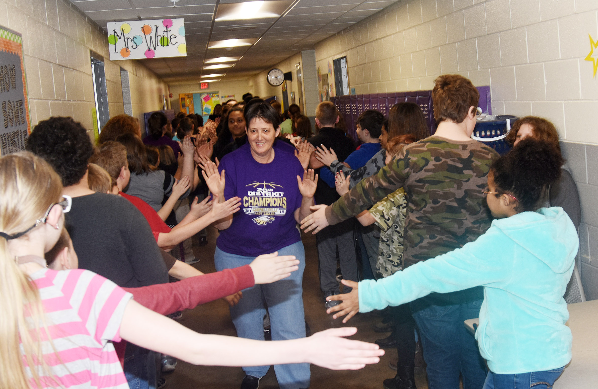 CHS girls' basketball assistant coach Katie Wilkerson and her players high-five CES students.