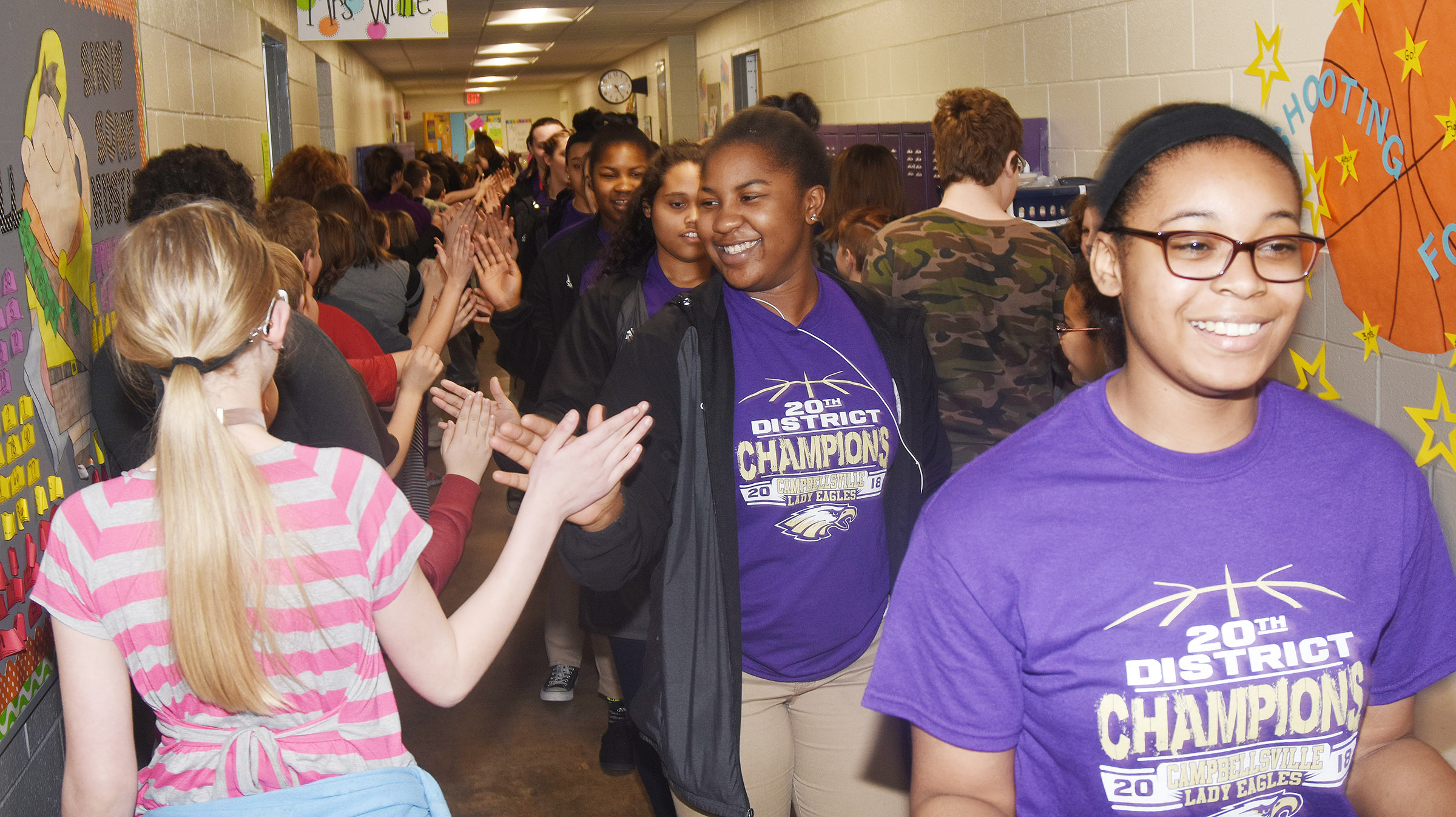 CHS girls' basketball player Vonnea Smith, a senior, and her teammates high-five CES students.