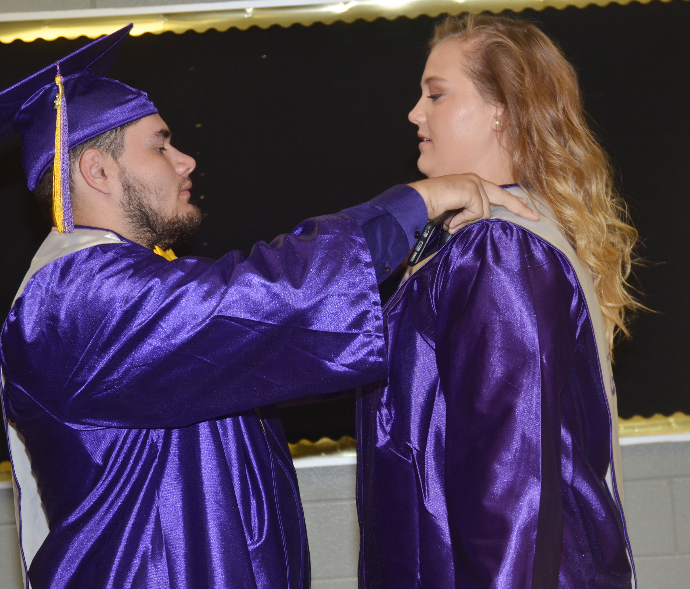 CHS senior Logan Brown helps classmate Brenna Wethington adjust her sash before graduation.