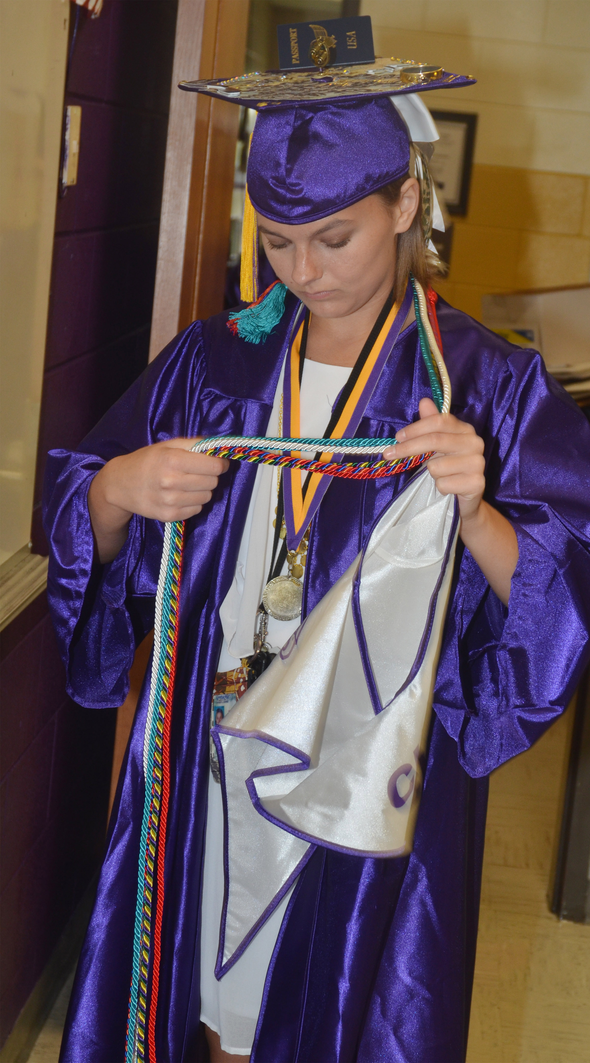 CHS senior Kyrsten Hill adjusts her honor cords before graduation.