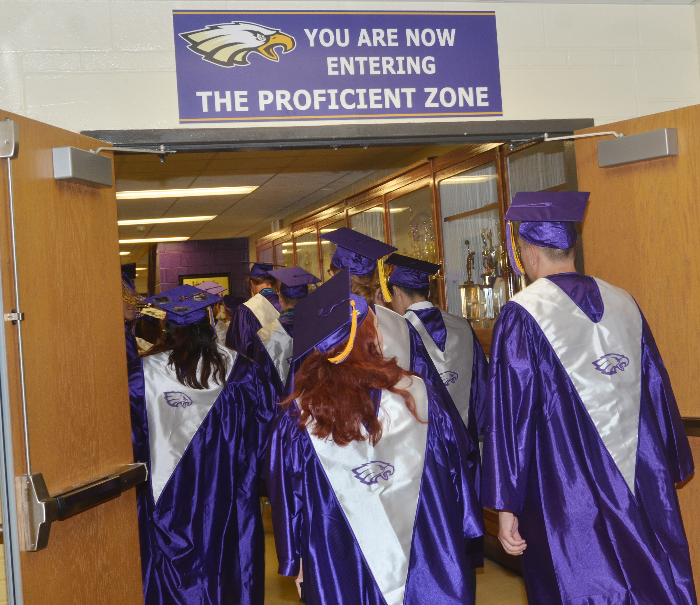 CHS seniors walk down the hallway to graduate.