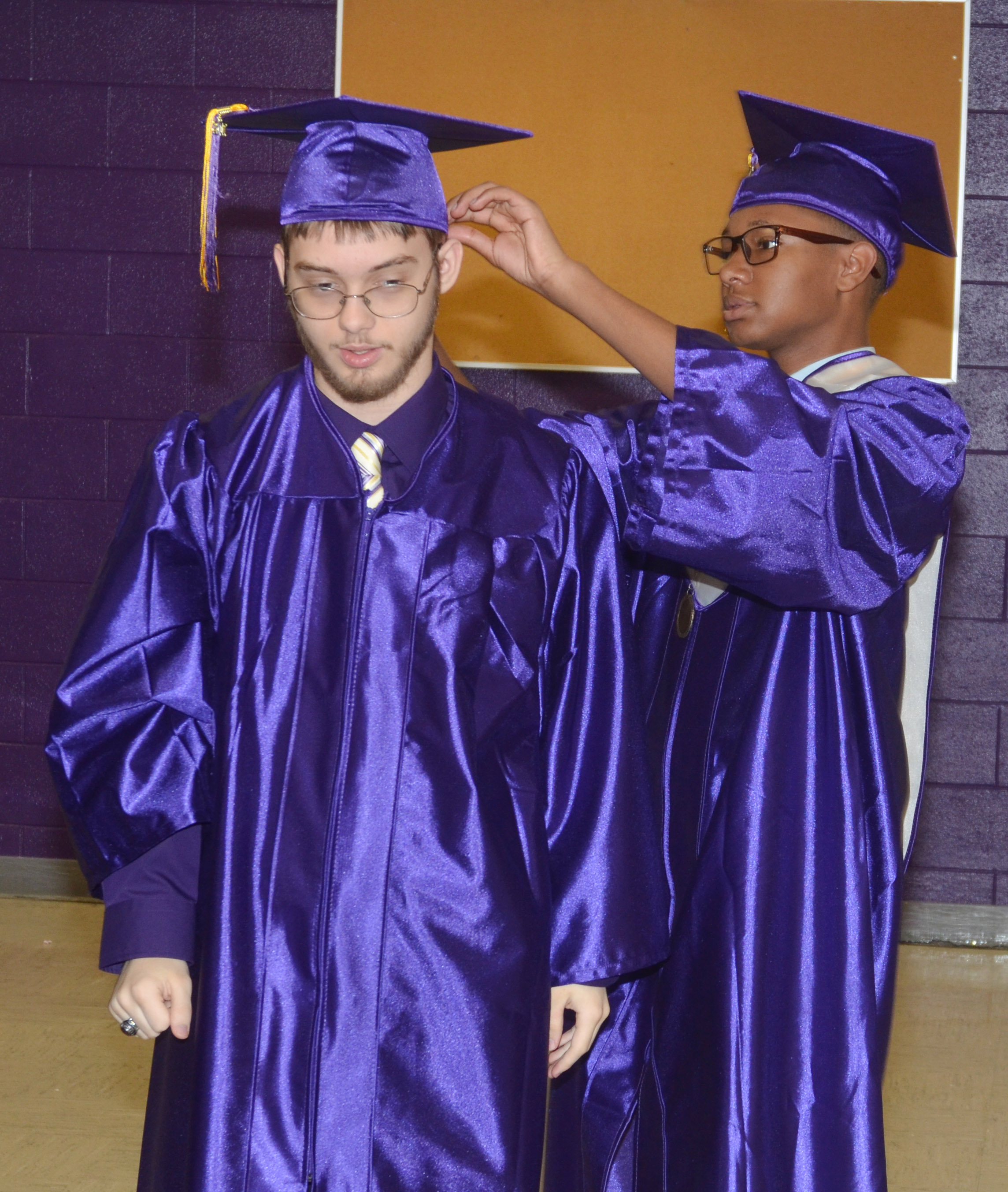 CHS senior Jaleel Cowan helps classmate Gabriel Clark with his cap.