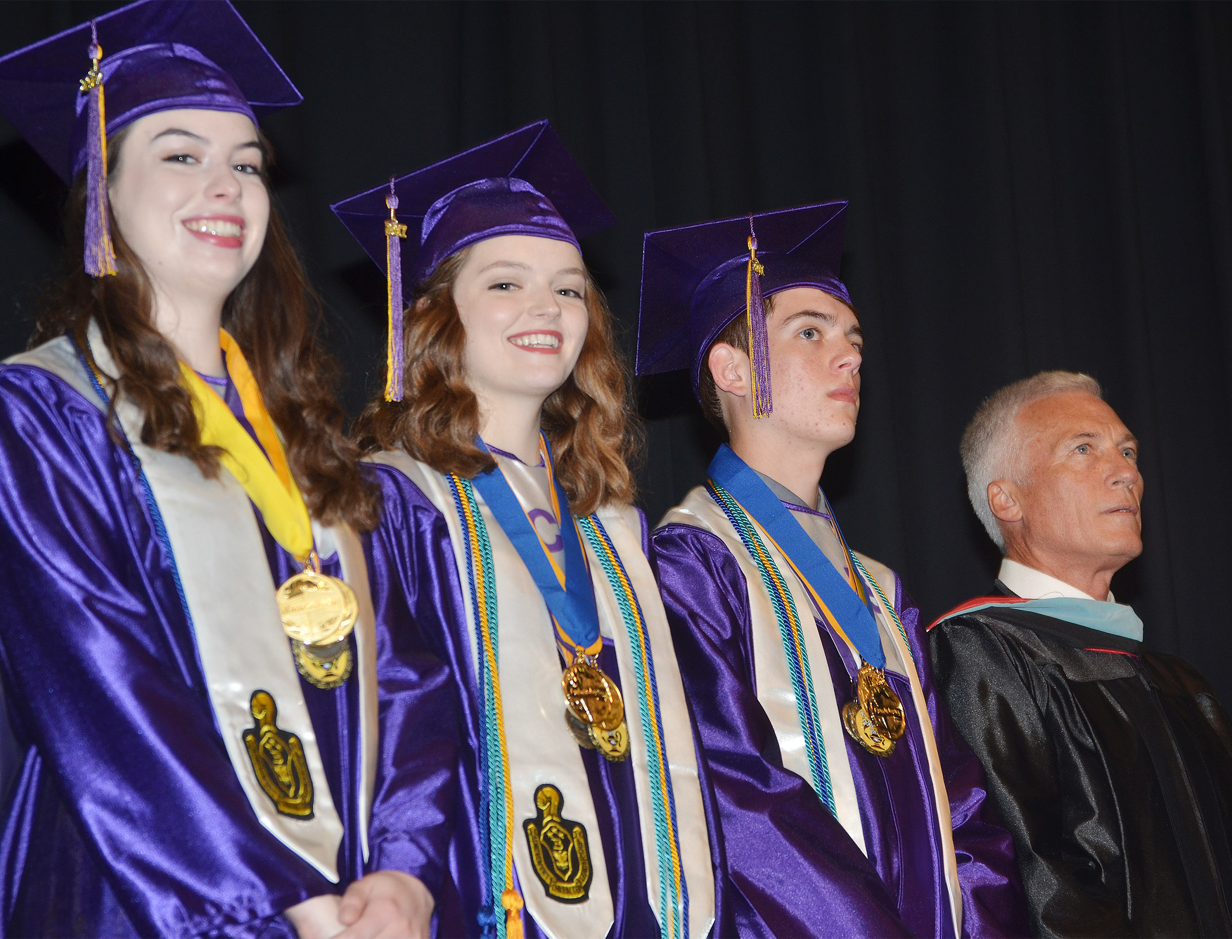 From left, CHS seniors Laura Lamb, Blair Lamb and Murphy Lamb stand with Campbellsville Independent Schools Superintendent Mike Deaton as they prepare to speak to their classmates.