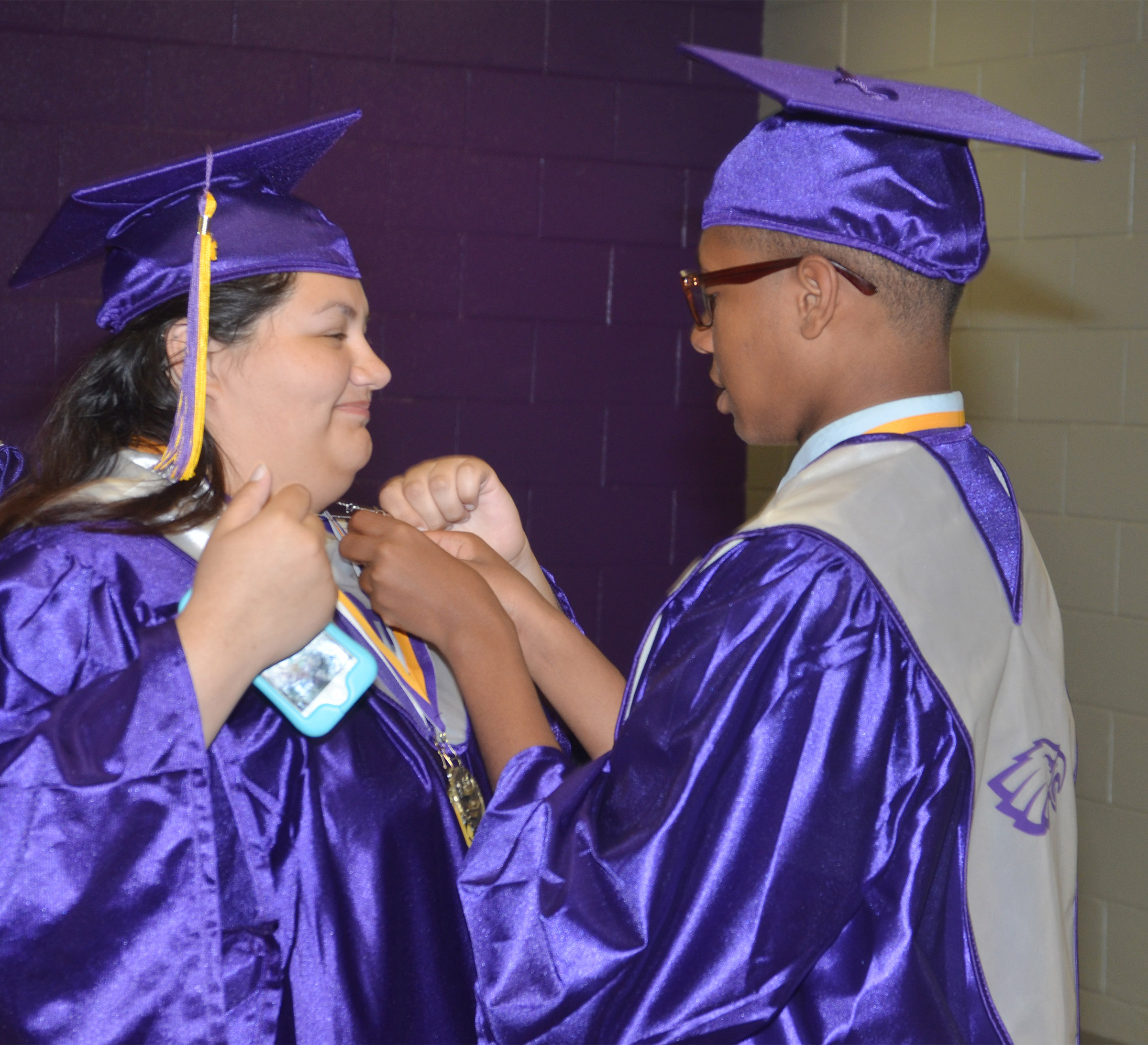 CHS senior Jaleel Cowan helps classmate Laura May Gutierrez with her cap.