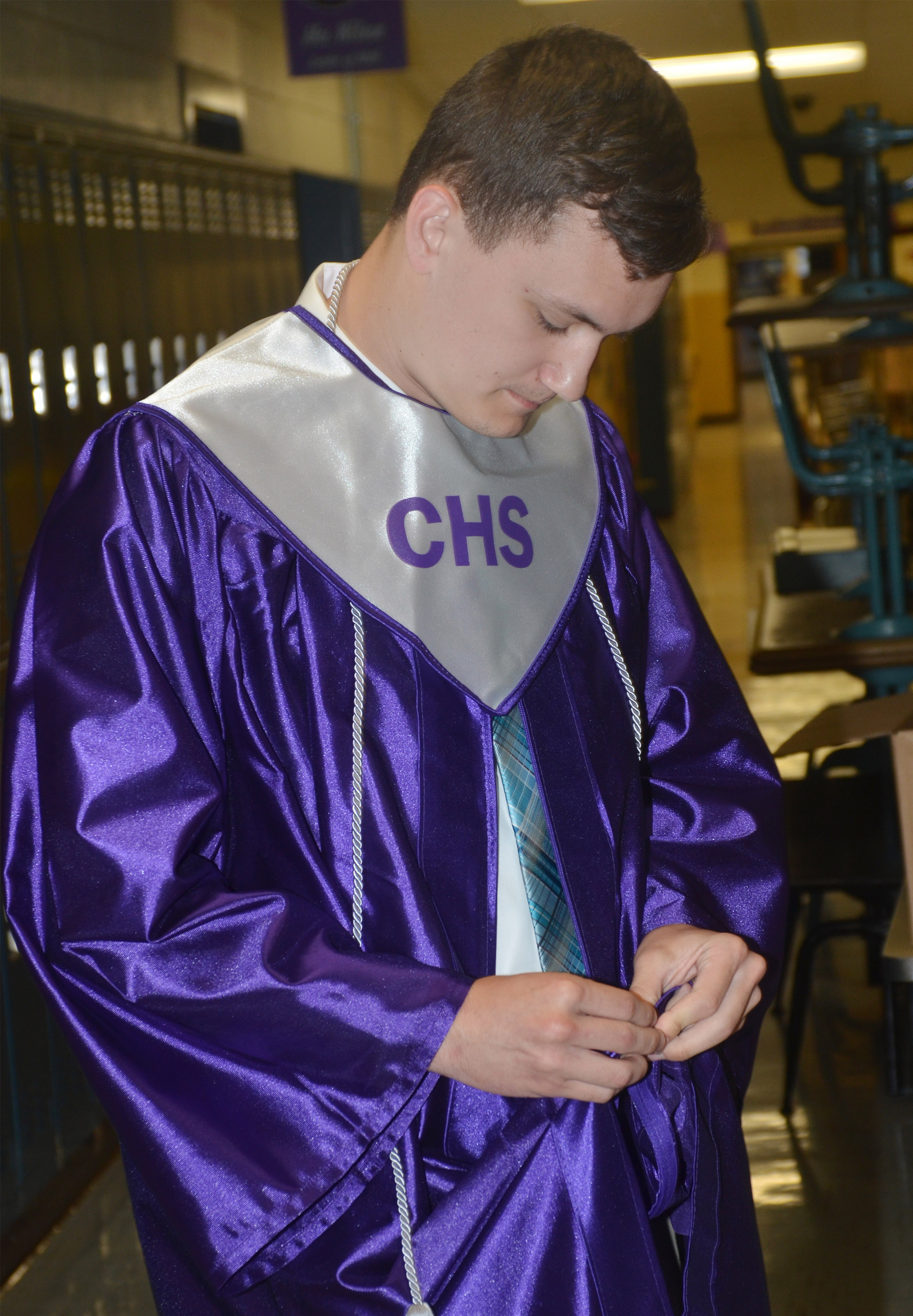 CHS senior Jonathan Rakes zips his gown before graduation.