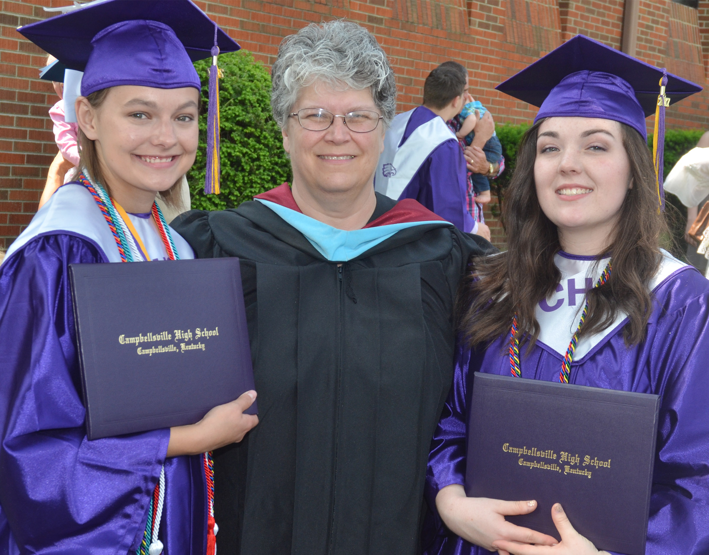 CHS art teacher Jo Ann Harris poses for a photo with two of her students who graduated, Kyrsten Hill, at left, and Tiffany Stagner.