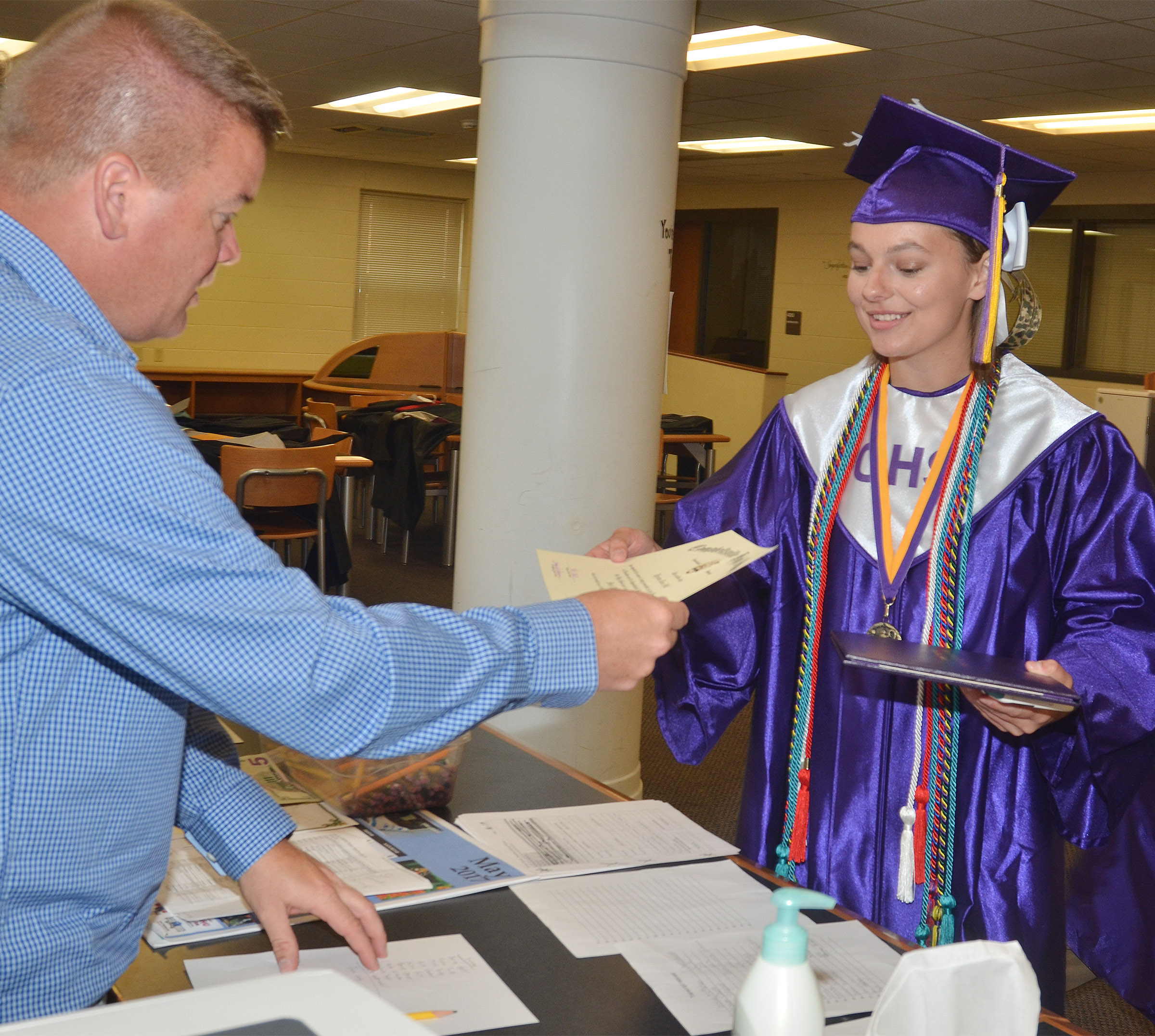 CHS graduate Kyrsten Hill receives her diploma from teacher Dale Estes.