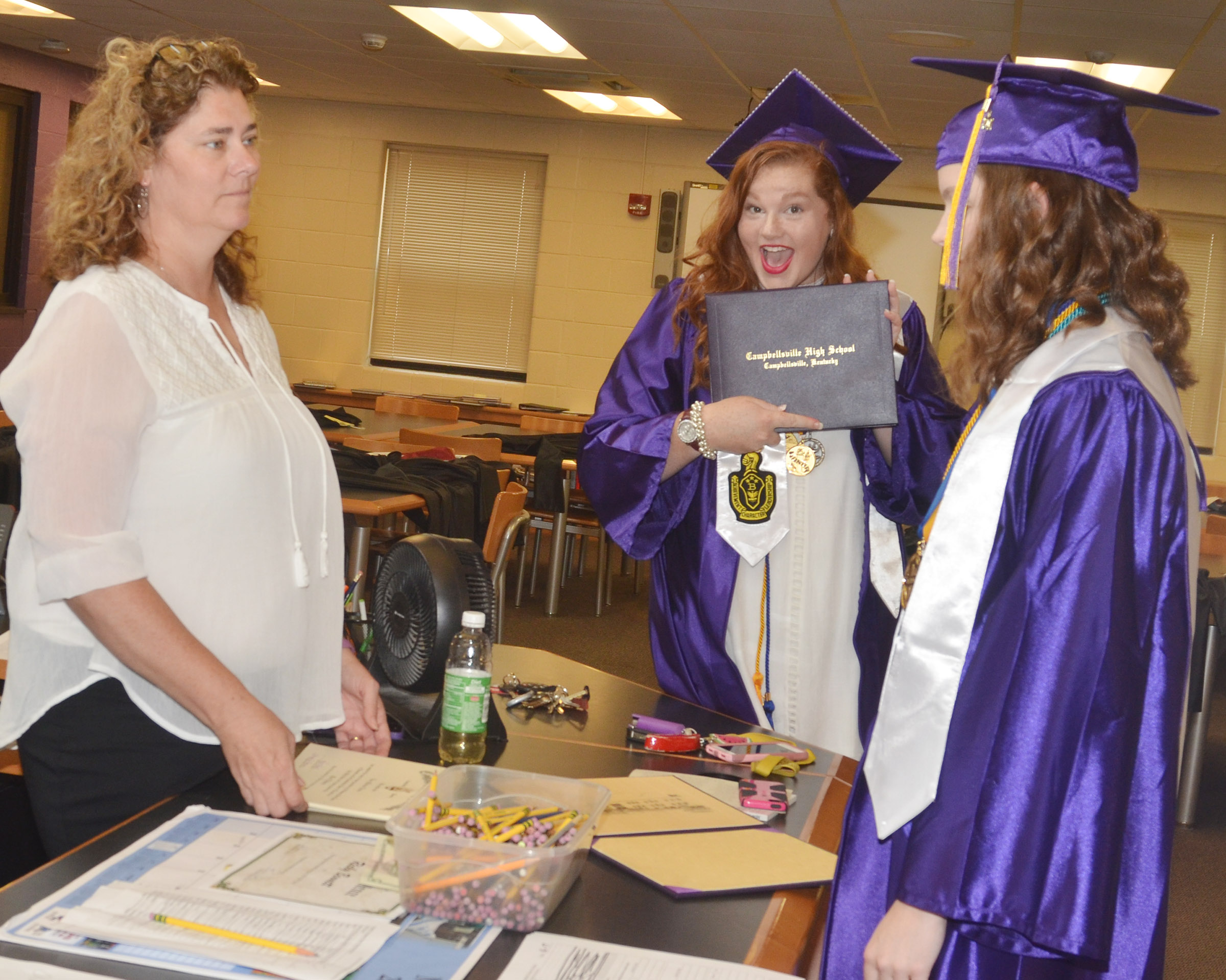 CHS graduate Mallory Haley poses for a photo with her diploma as teacher Tammy Wilson talks with graduate Blair Lamb.