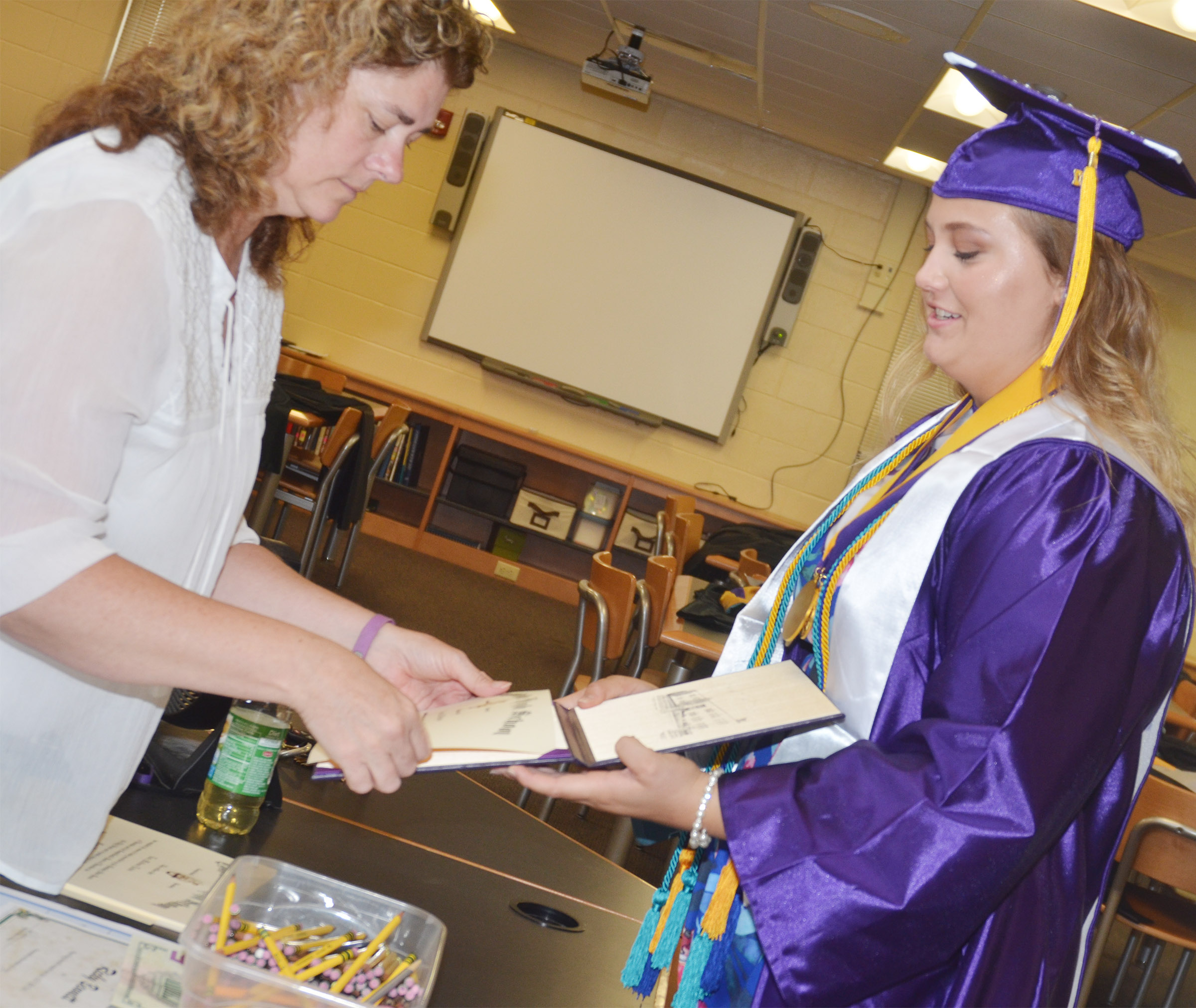 CHS teacher Tammy Wilson helps graduate Brenna Wethington with her diploma