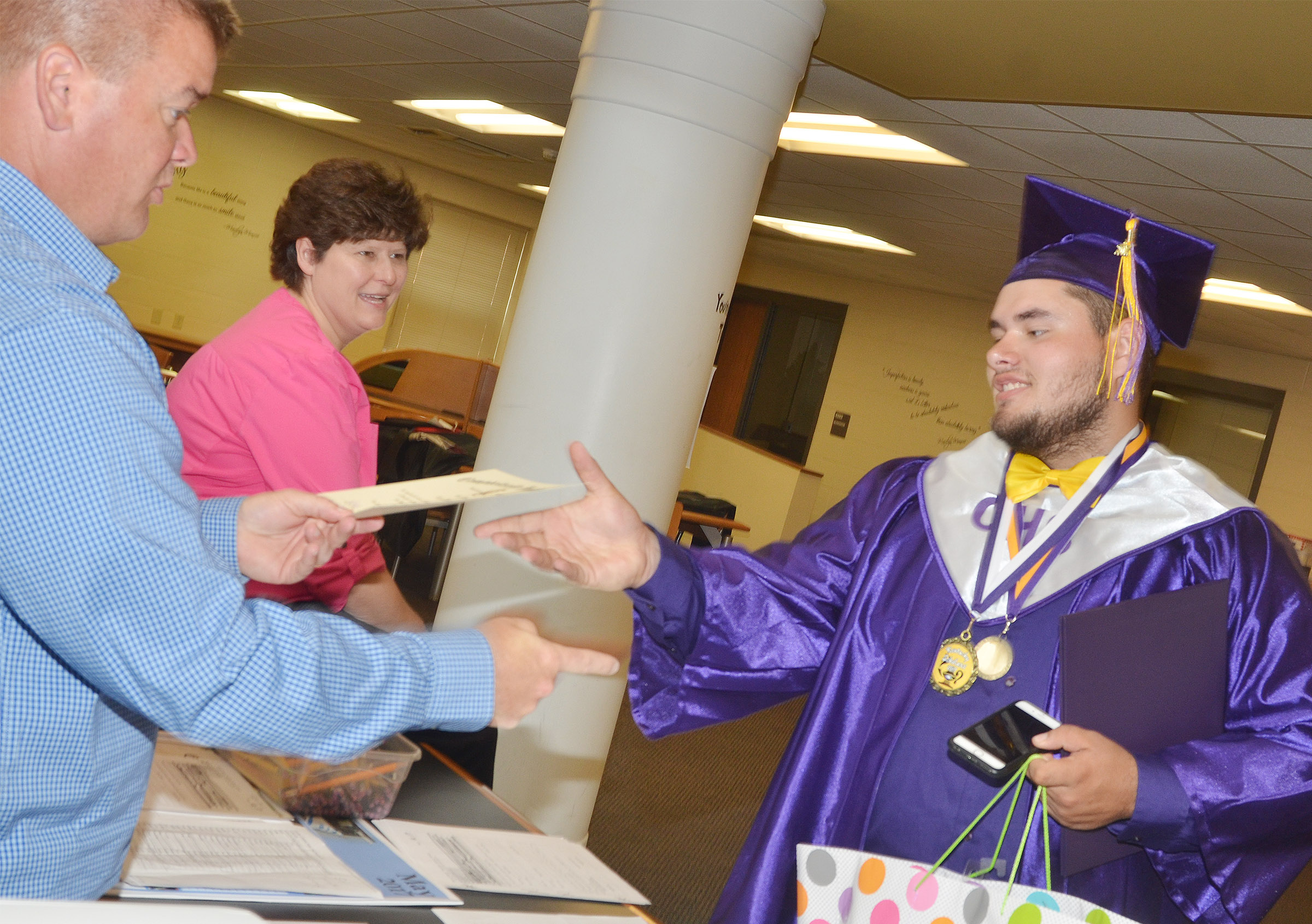 CHS graduate Logan Brown receives his diploma from his football coach Dale Estes.