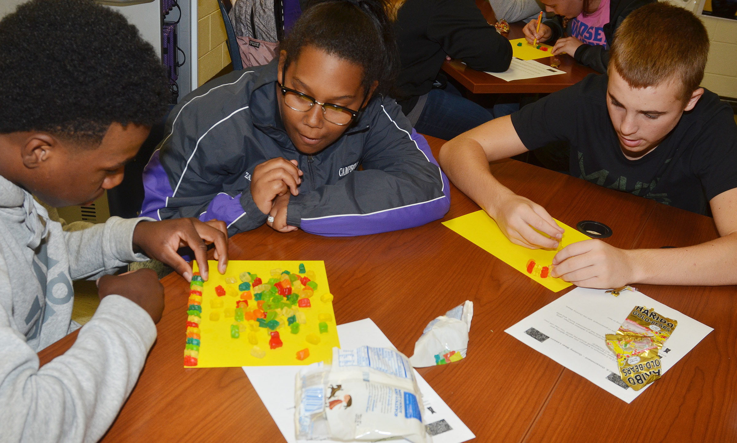 From left, CHS sophomores Malachi Corley, Zaria Cowan and Tyler Gribbins build their gummy bear government models.