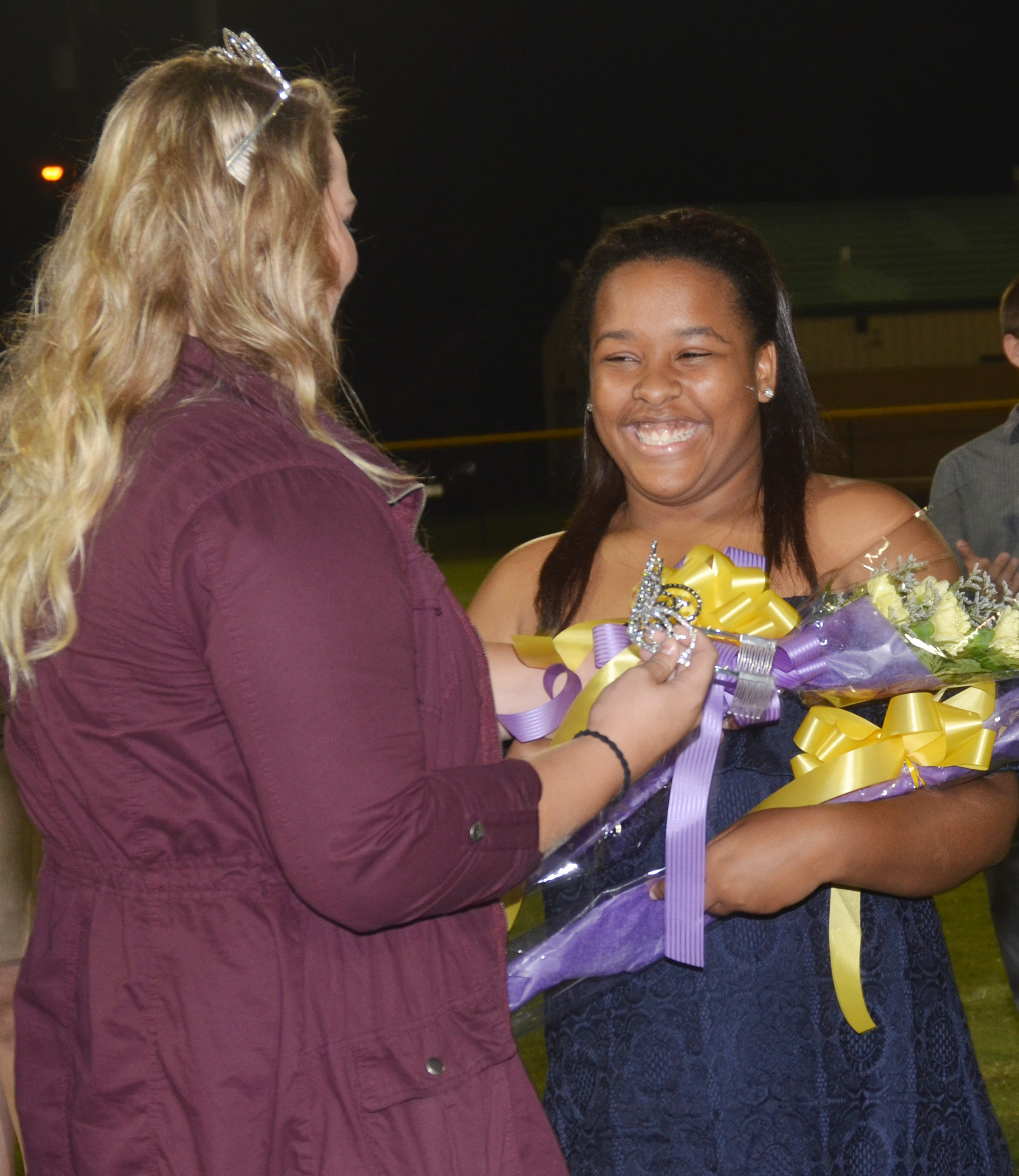CHS senior Kayla Young smiles as graduate Brenna Wethington crowns her as homecoming queen.