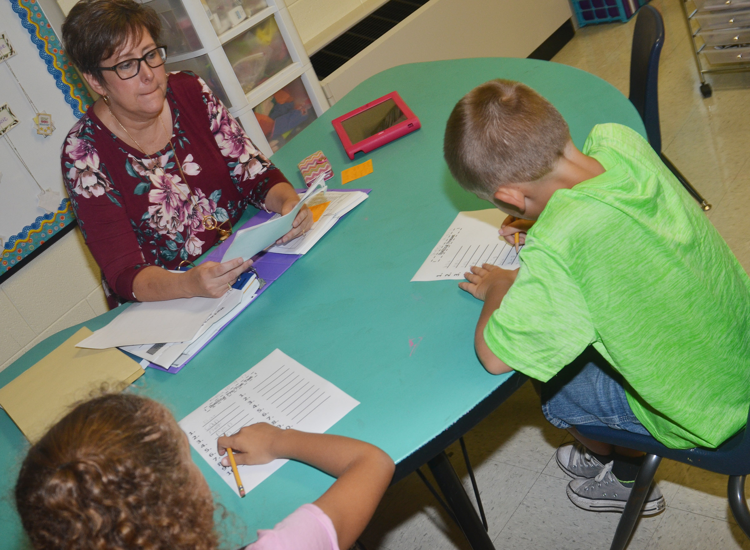 CES second-grade teacher Lynne Horn gives Keiava Thompson, at left, and Seeley Whitaker a pre-test.
