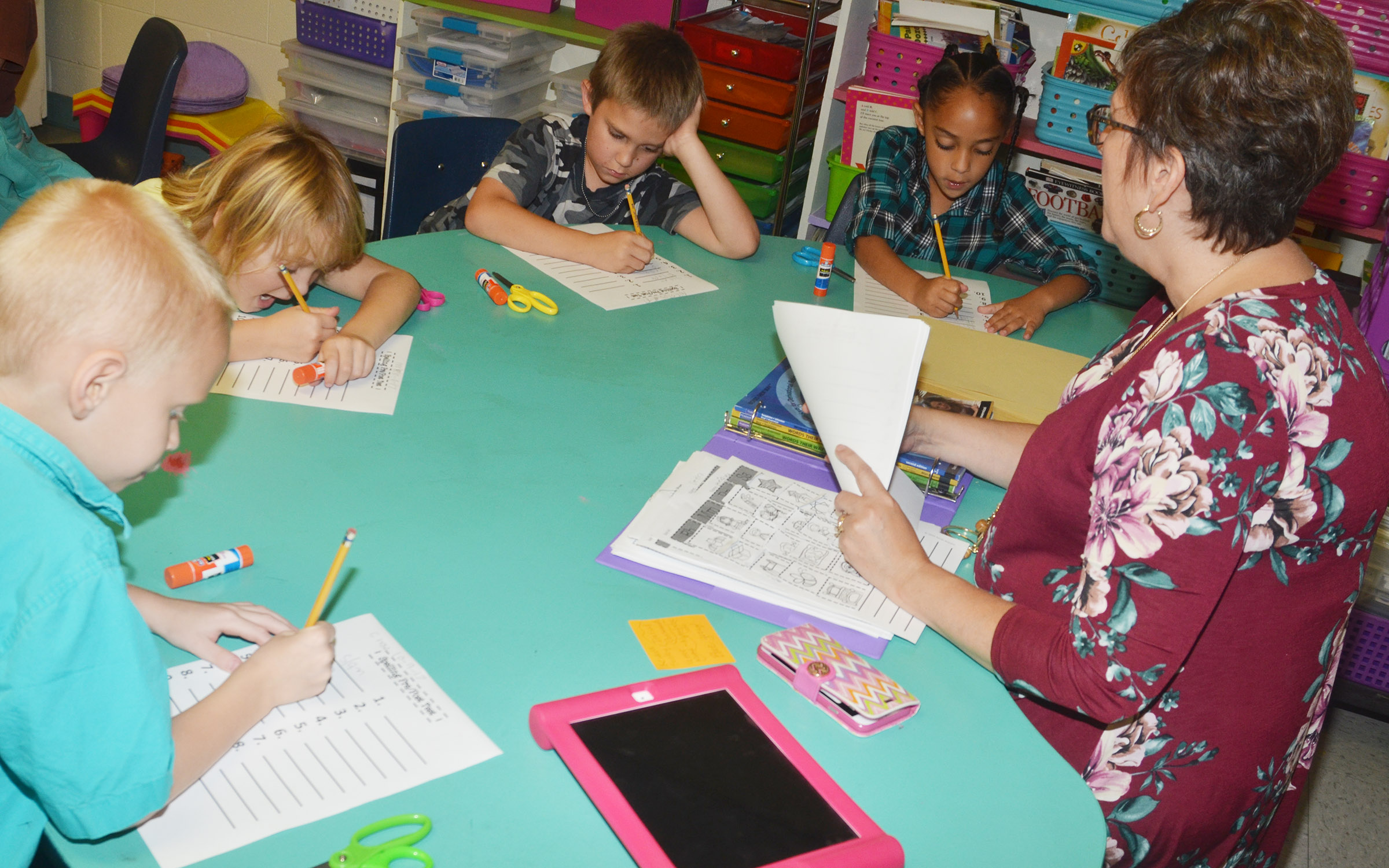 CES second-grade teacher Lynne Horn administers a pre-test for students, from left, Chase Gabbert, Mylee Bell, Nikolas Torres and Essence Hunter.