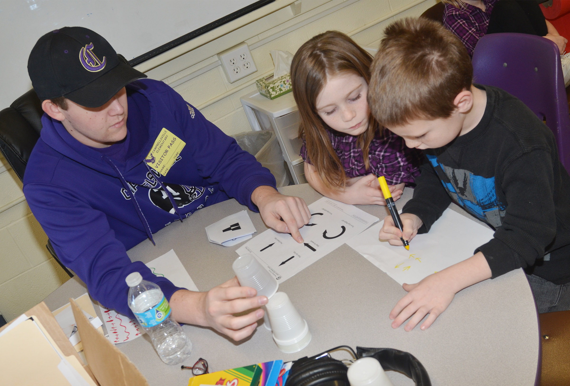 CHS senior Jared Brewster teaches CES first-graders Izzy Brunelle, at left, and James Brunner about computer coding.