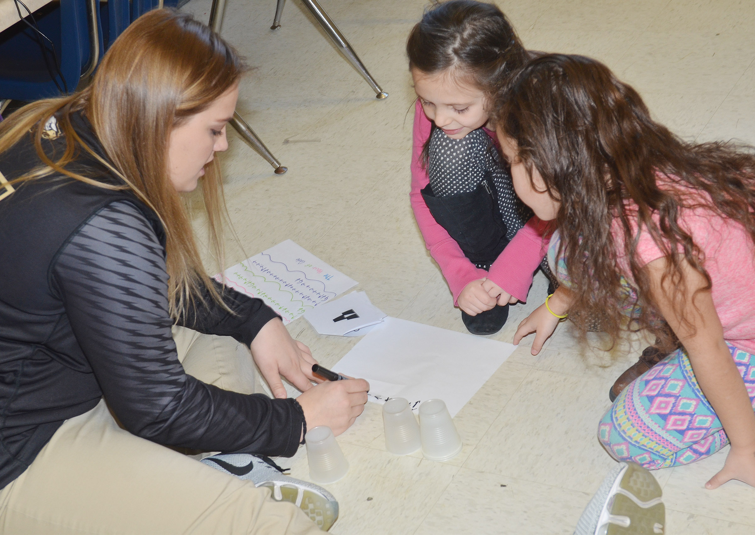 CHS senior Brenna Wethington teaches CES first-graders Serenity Taylor, center, and Nadia Taylor about computer coding.