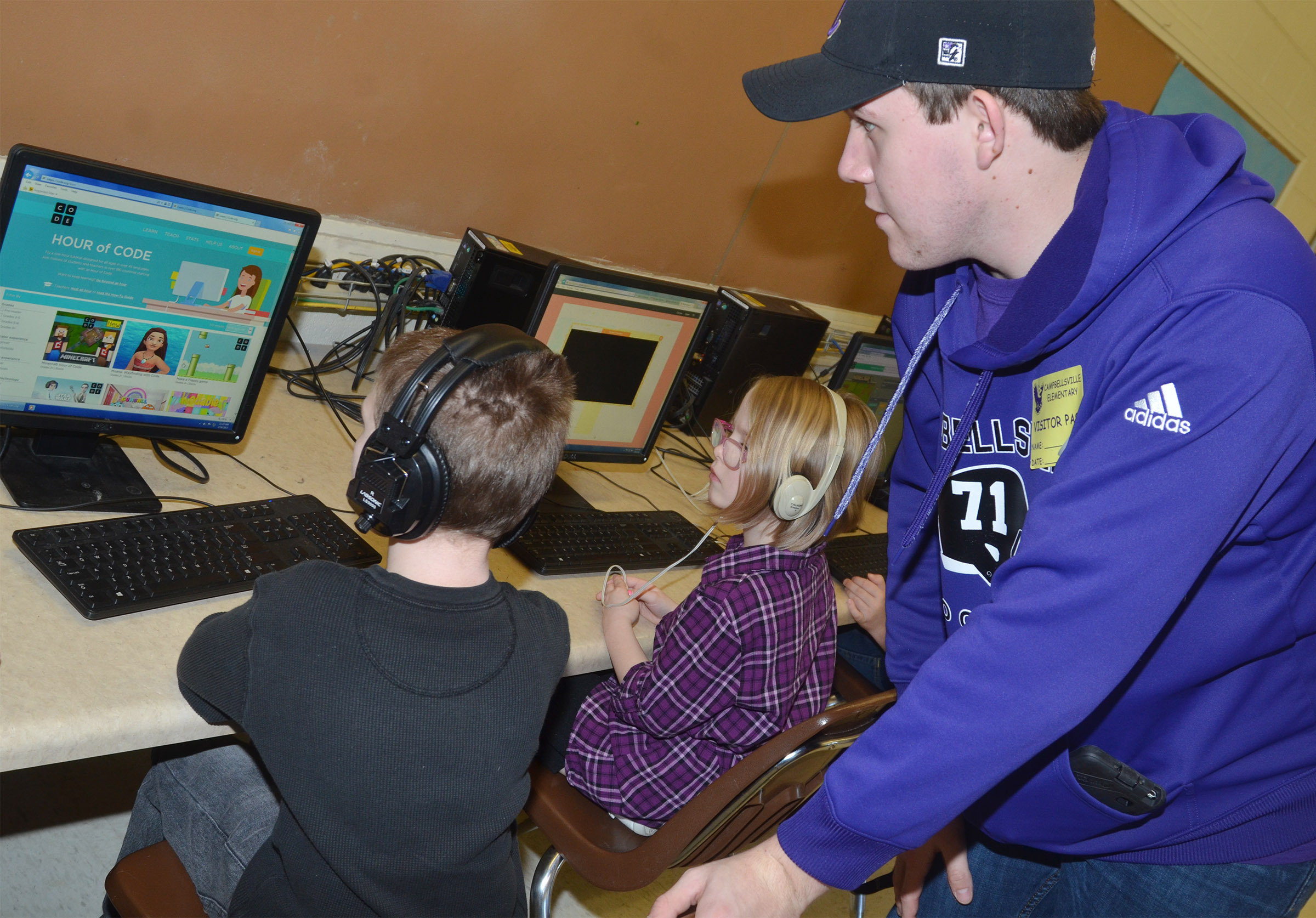 CHS senior Jared Brewster helps CES first-graders learn about computer coding.