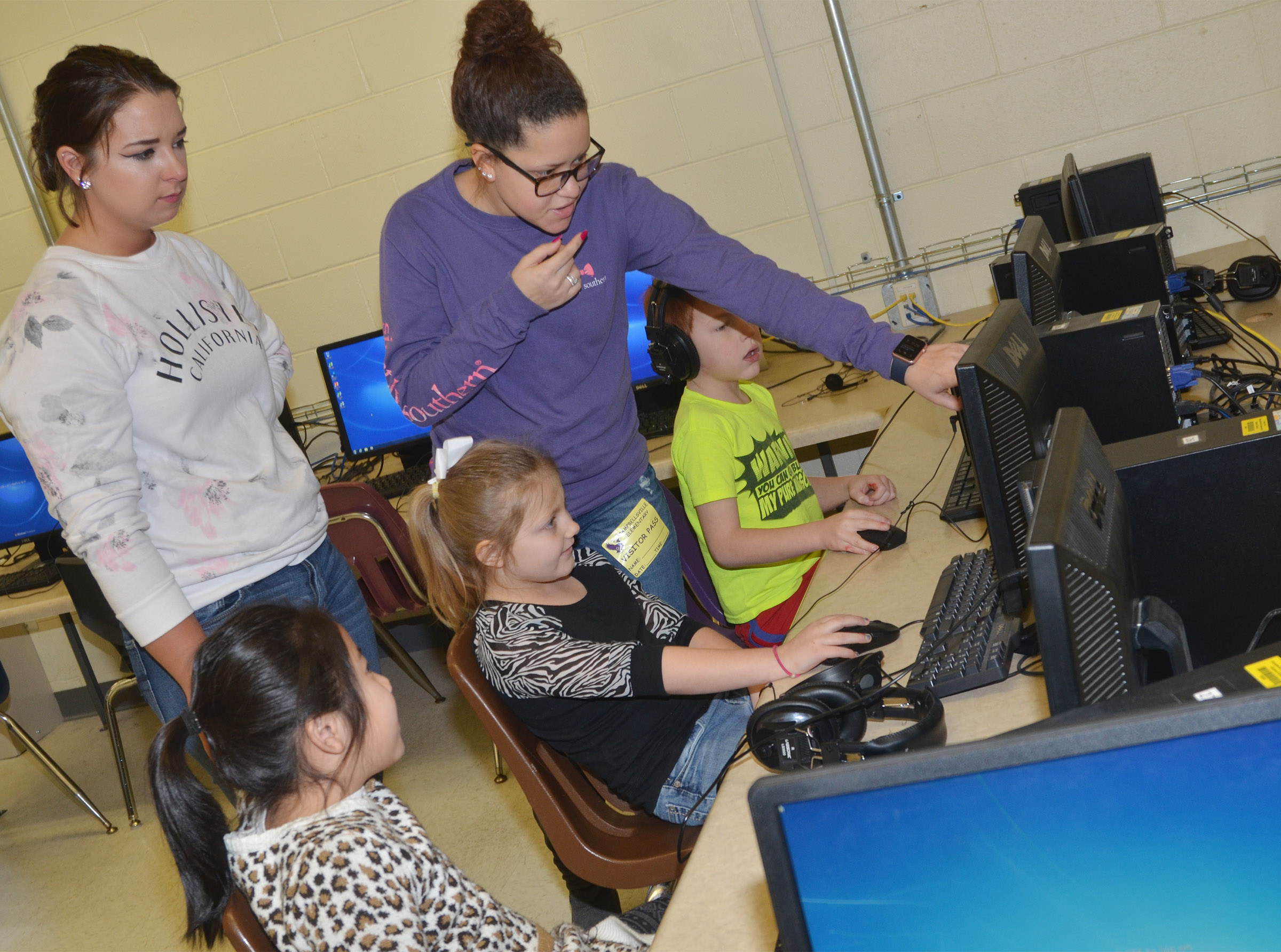 CHS seniors Kaylie Morris, at left, and Breanna Spaulding teach CES first-graders about computer coding.