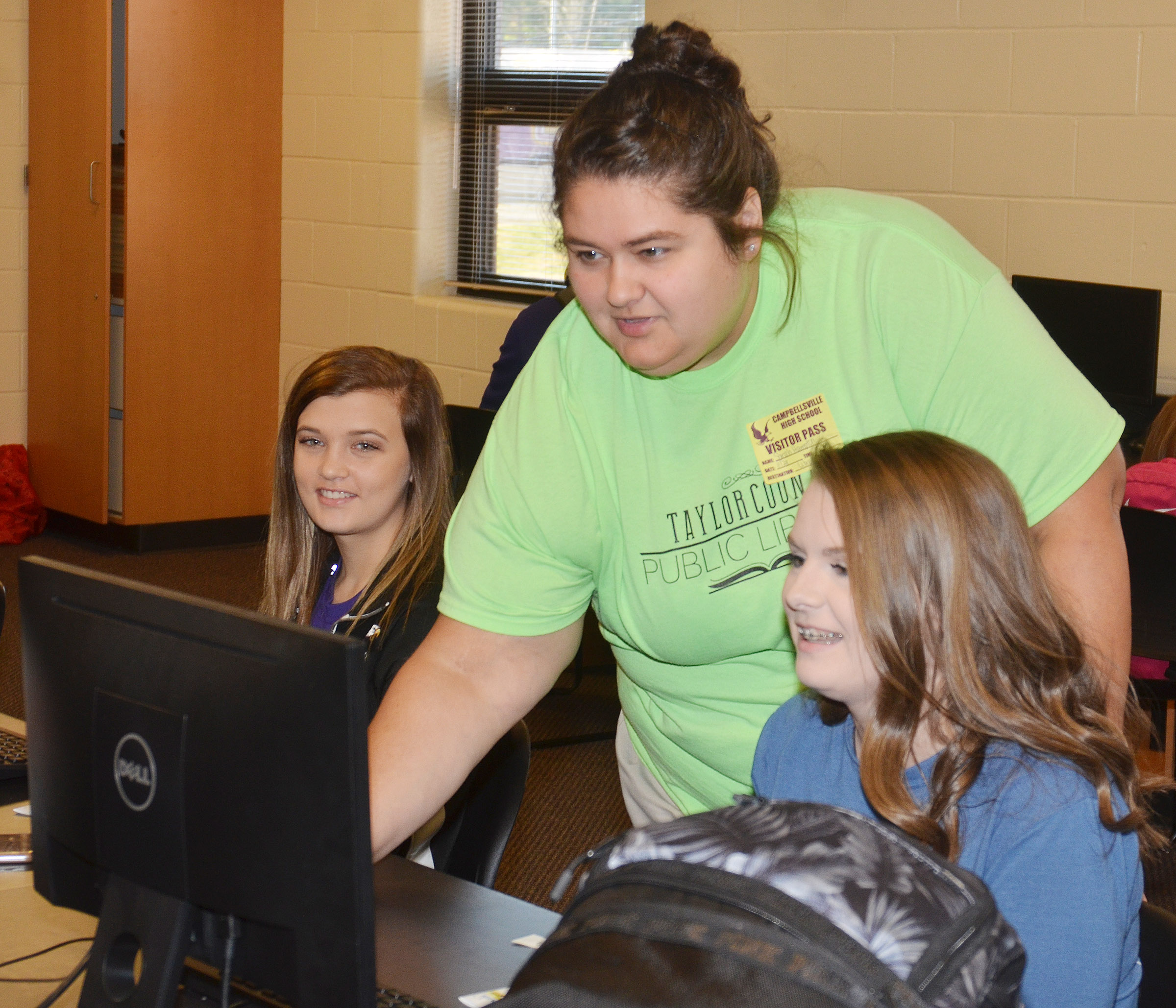 Sarah Hampton of Taylor County Public Library helps CHS freshmen Carly Adams, at left, and Taylor Knight register for access to the library's free digital services.