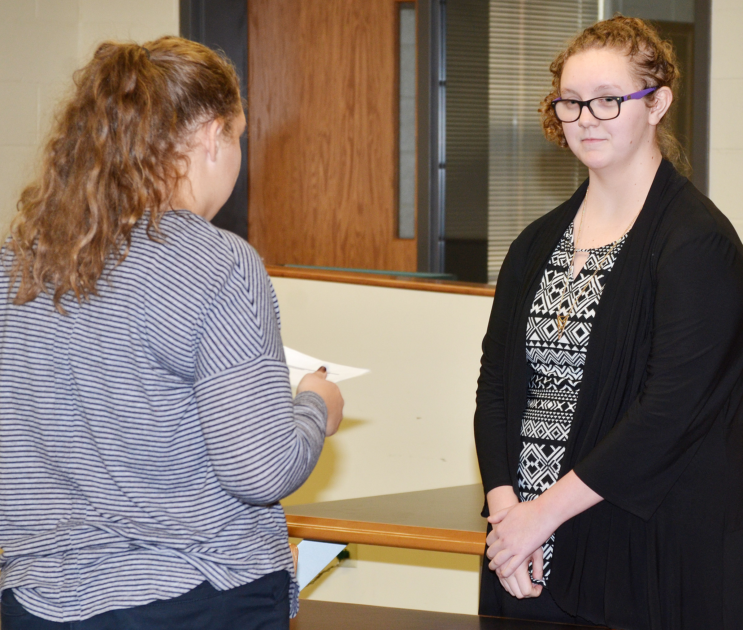 CHS sophomore Abie Angel, portraying a bailiff, swears in classmate Emily Rodgers as she testifies.