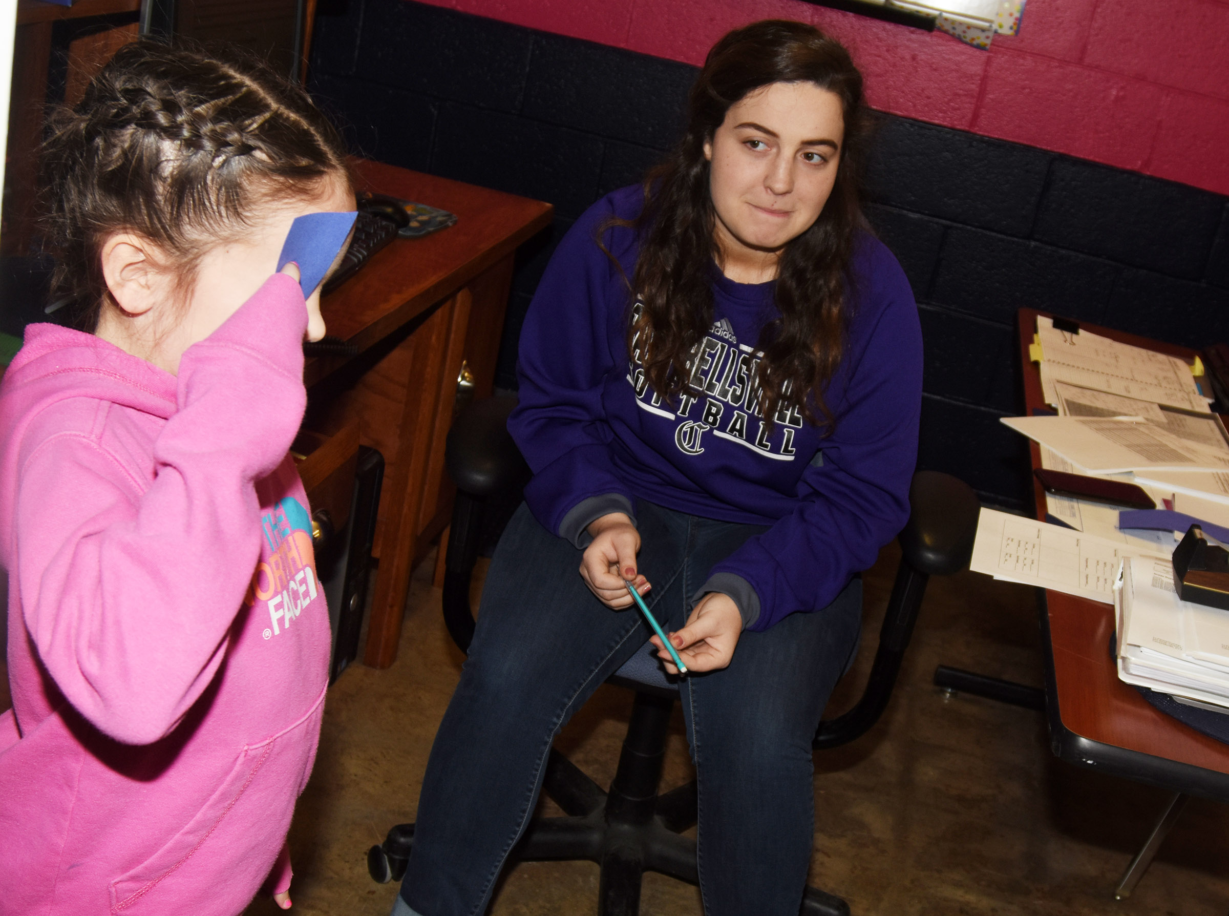 CHS senior Caitlin Bright listens as CES first-grader Serenity Jones undergoes an eye exam. Bright is completing an internship with Beth Wiedewitsch, who is a guidance counselor at Campbellsville elementary and middle schools.