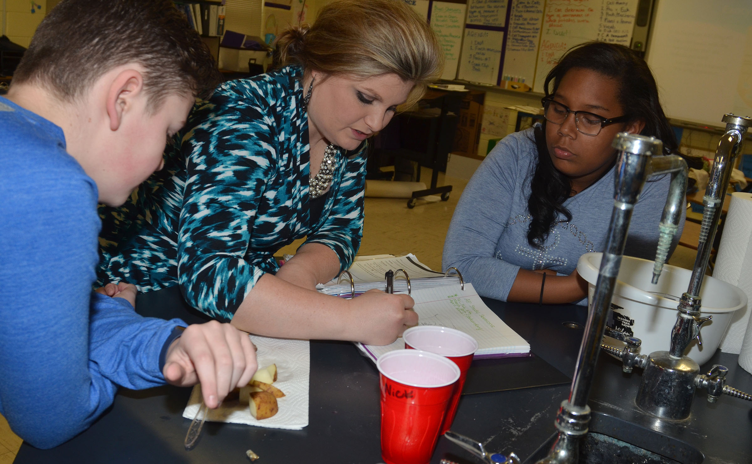 CHS AP biology teacher Lauren Bennett helps freshmen Gavin Johnson, at left, and Zaria Cowan understand what happens during osmosis.