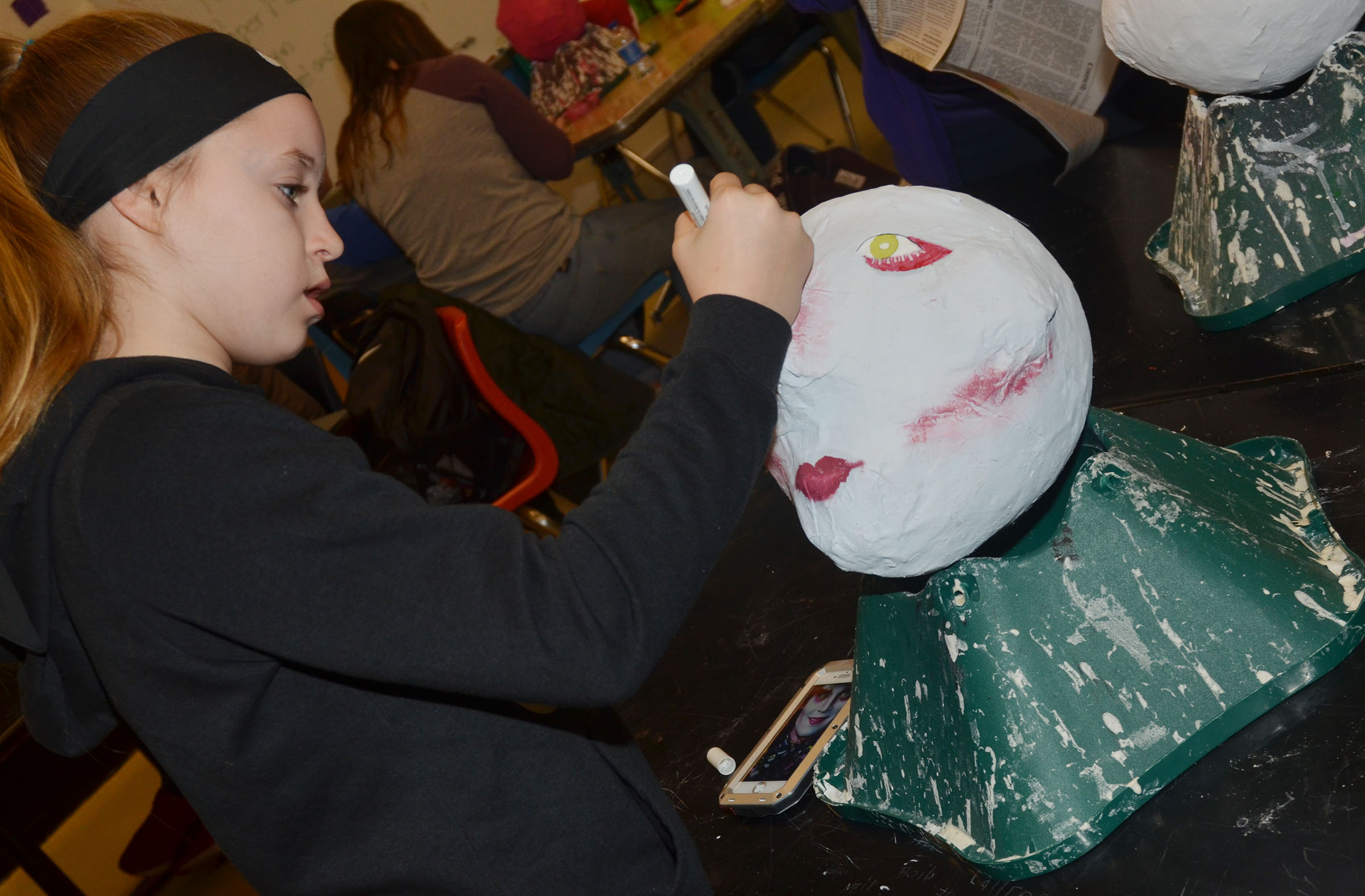 Campbellsville Middle School seventh-grader Rylee Petett paints her paper mache sculpture.