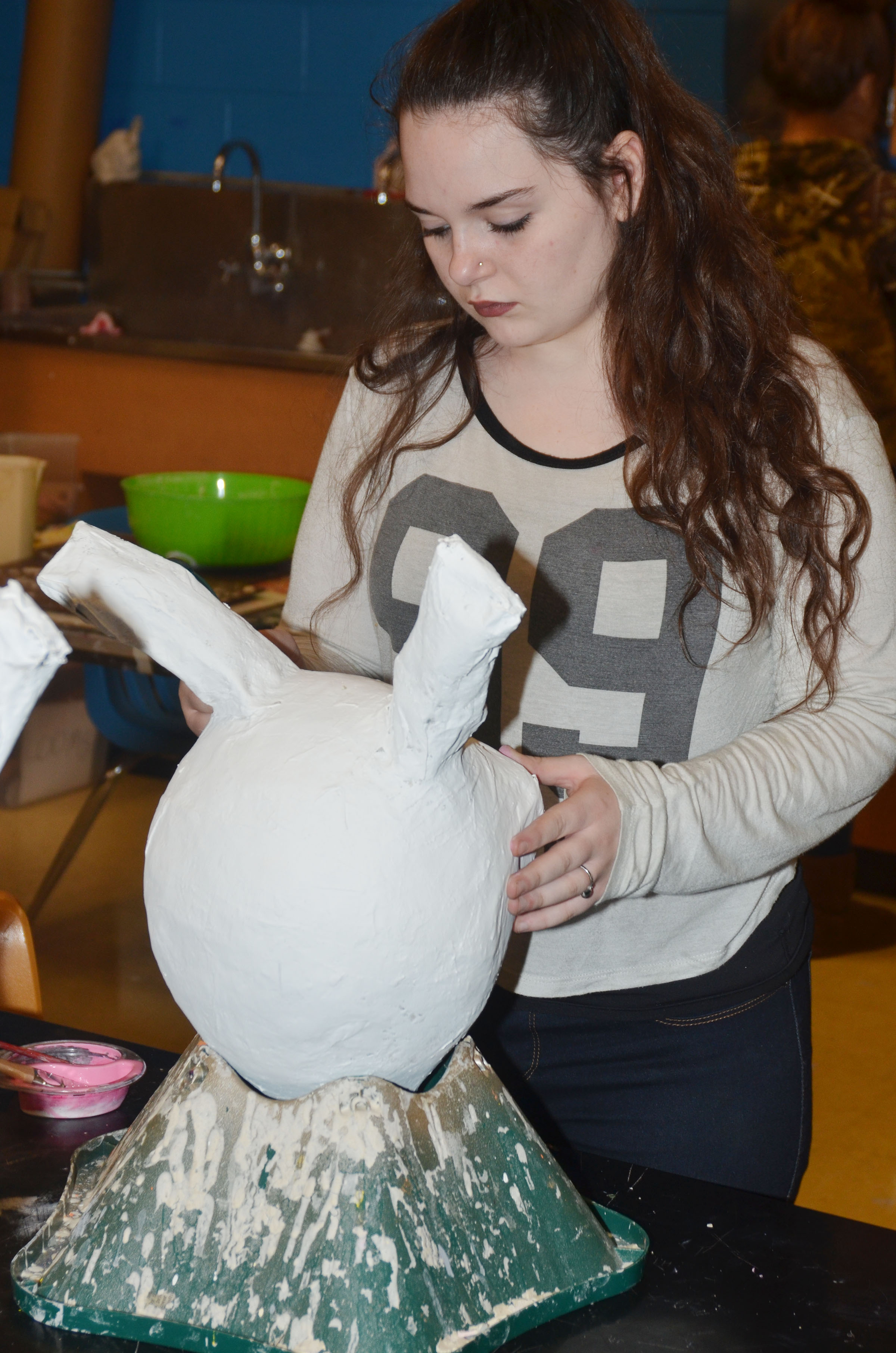 CHS freshman Summer Edwards paints her paper mache sculpture.