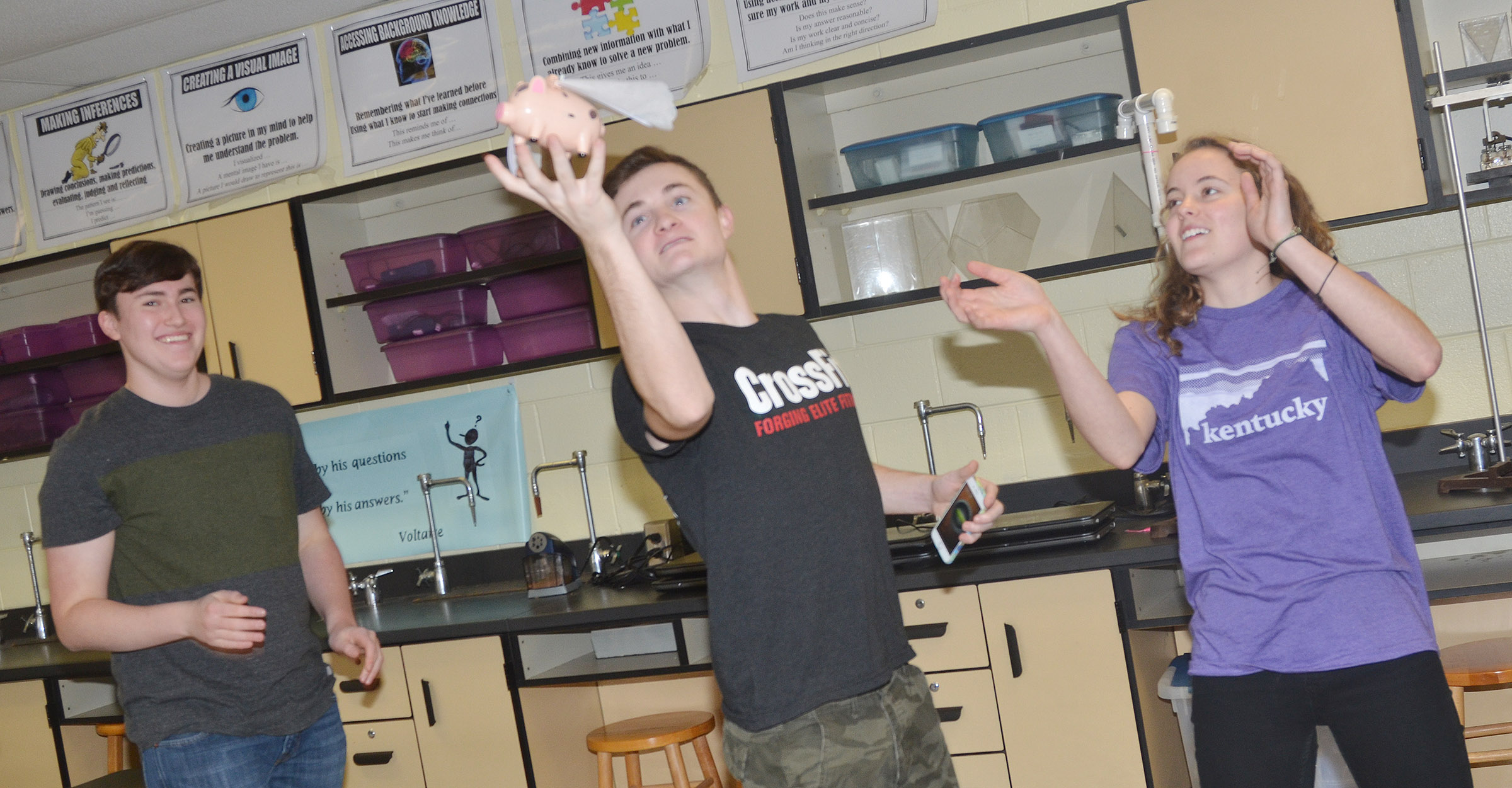 "From left, CHS senior Zack Settle, junior Bryce Richardson and senior Caroline McMahan watch their pig ""fly"" around the room."