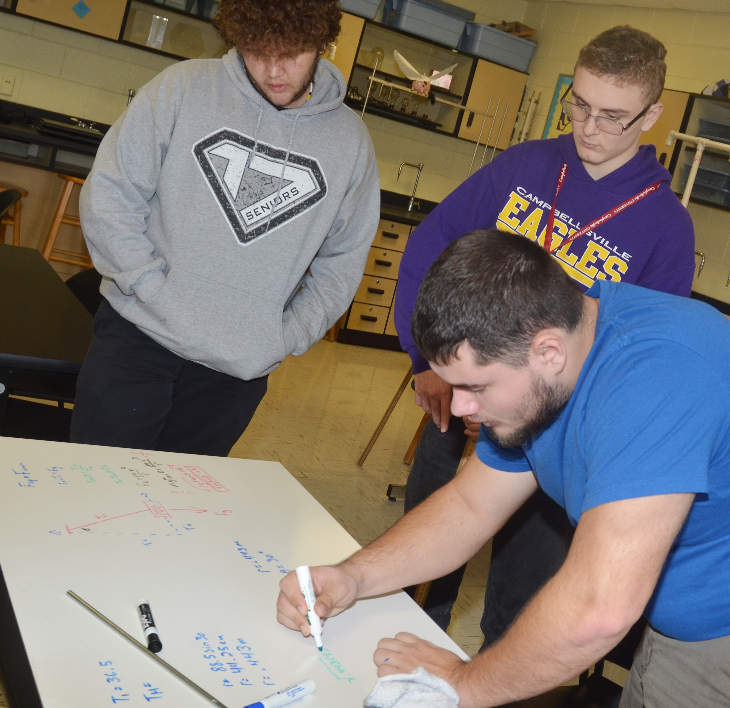 "From left, CHS seniors Dalton Ballentine, Ben Rafferty and Logan Brown make some revisions to their equation after testing their pig's ability to ""fly."""