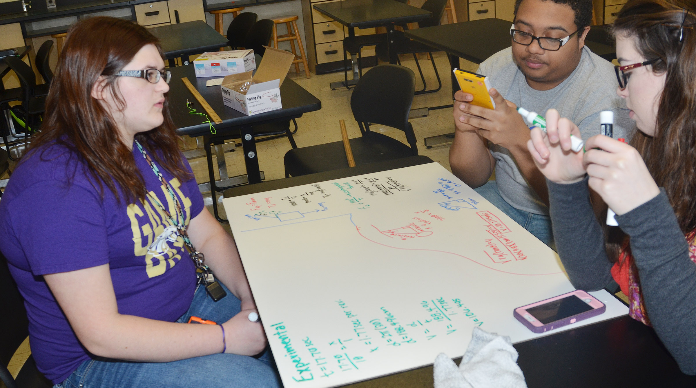 "From left, CHS seniors Vera Brown, Ricky Smith-Cecil and Laura Lamb write their equation after making their pig ""fly."""