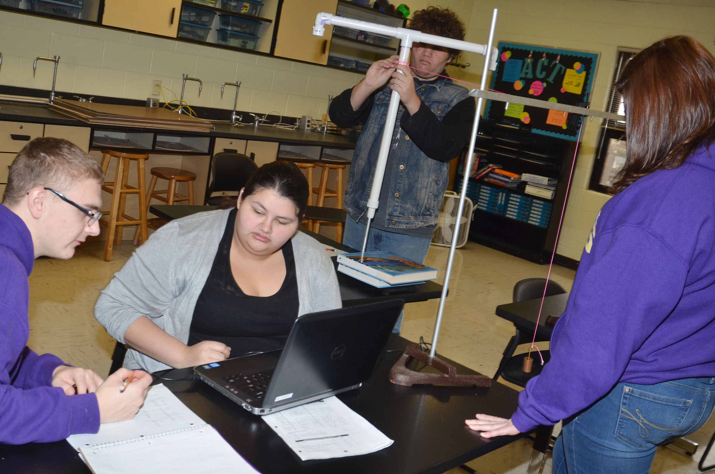 CHS seniors, from left, Ben Rafferty, Laura May Gutierrez, Dalton Ballentine and Vera Brown perform their experiment.