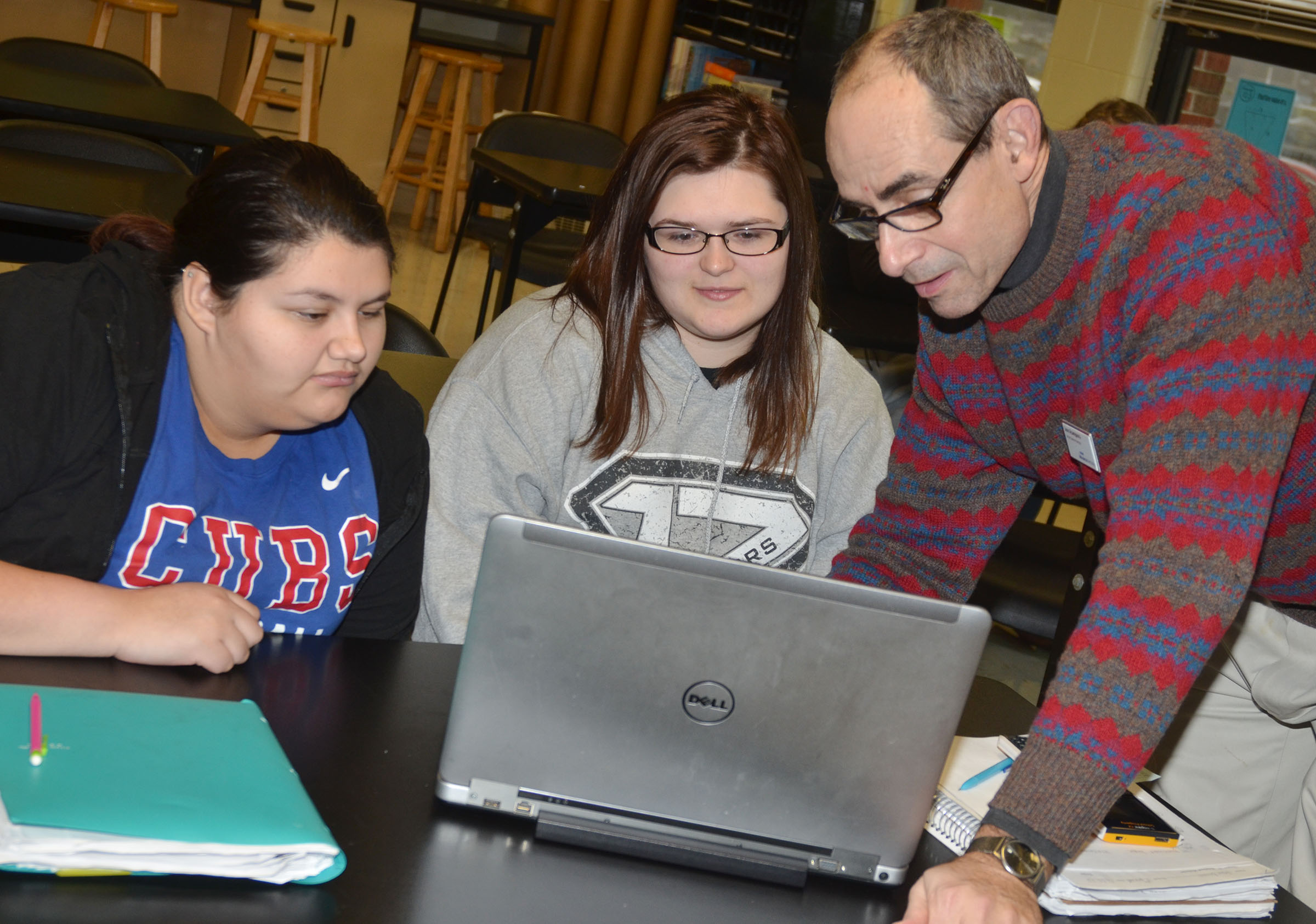 Lew Acampora, senior science director with AdvanceKentucky, works with CHS seniors Laura May Gutierrez, at left, and Vera Brown as they use the Logger Pro software.