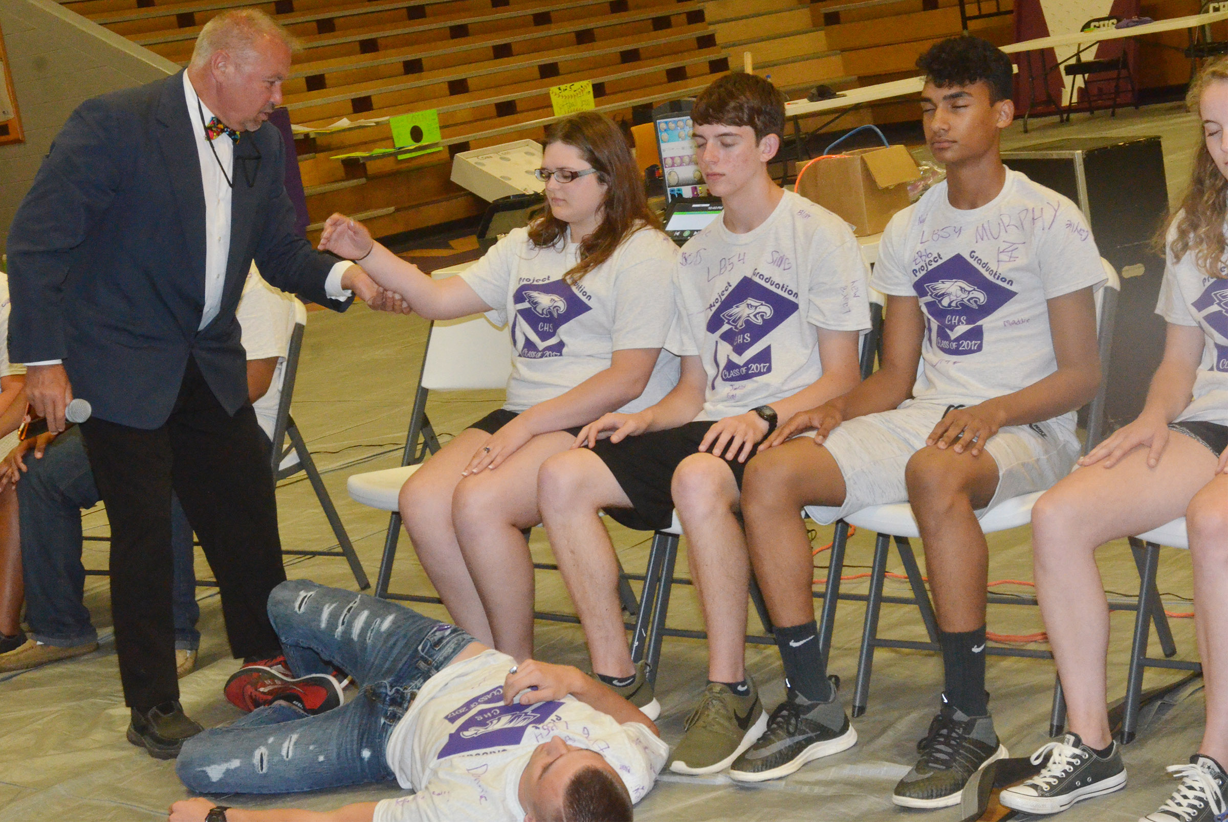 Magician Mark Comley hypnotizes CHS senior Vera Brown and her classmates.
