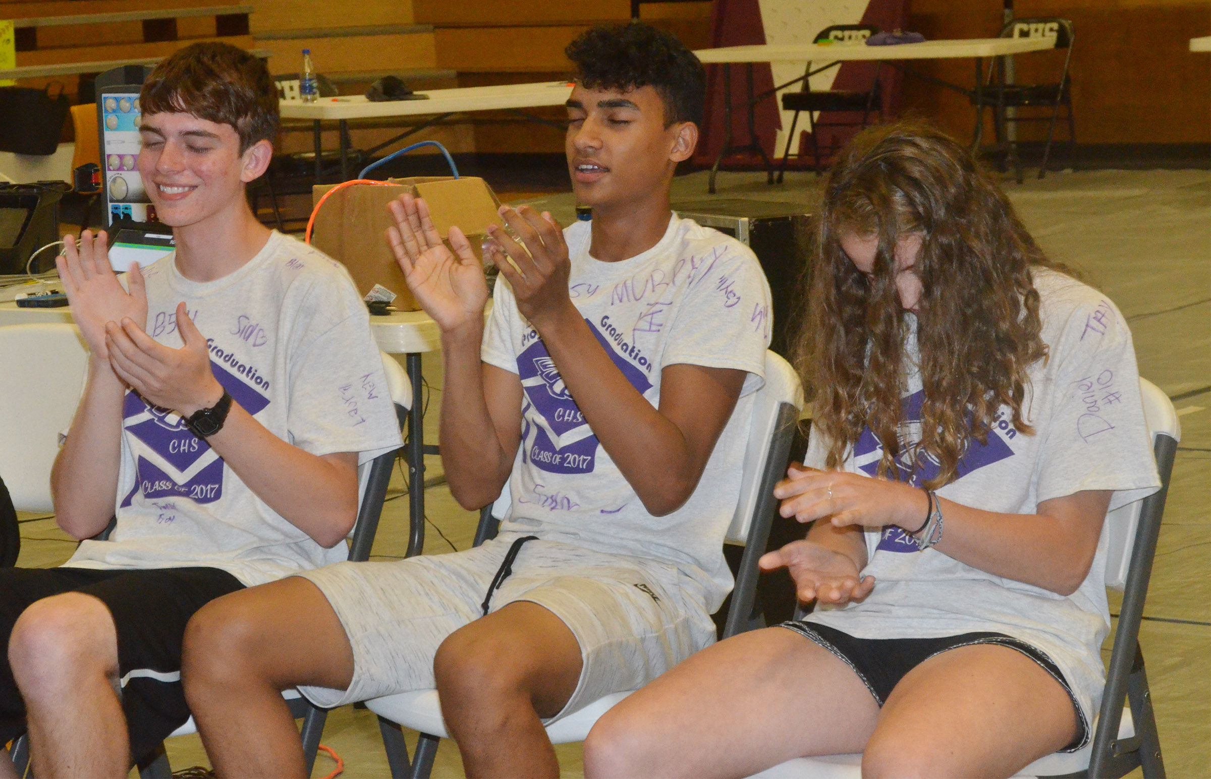 CHS seniors, from left, Murphy Lamb, Daniel Silva and Caroline McMahan clap while under hypnosis.