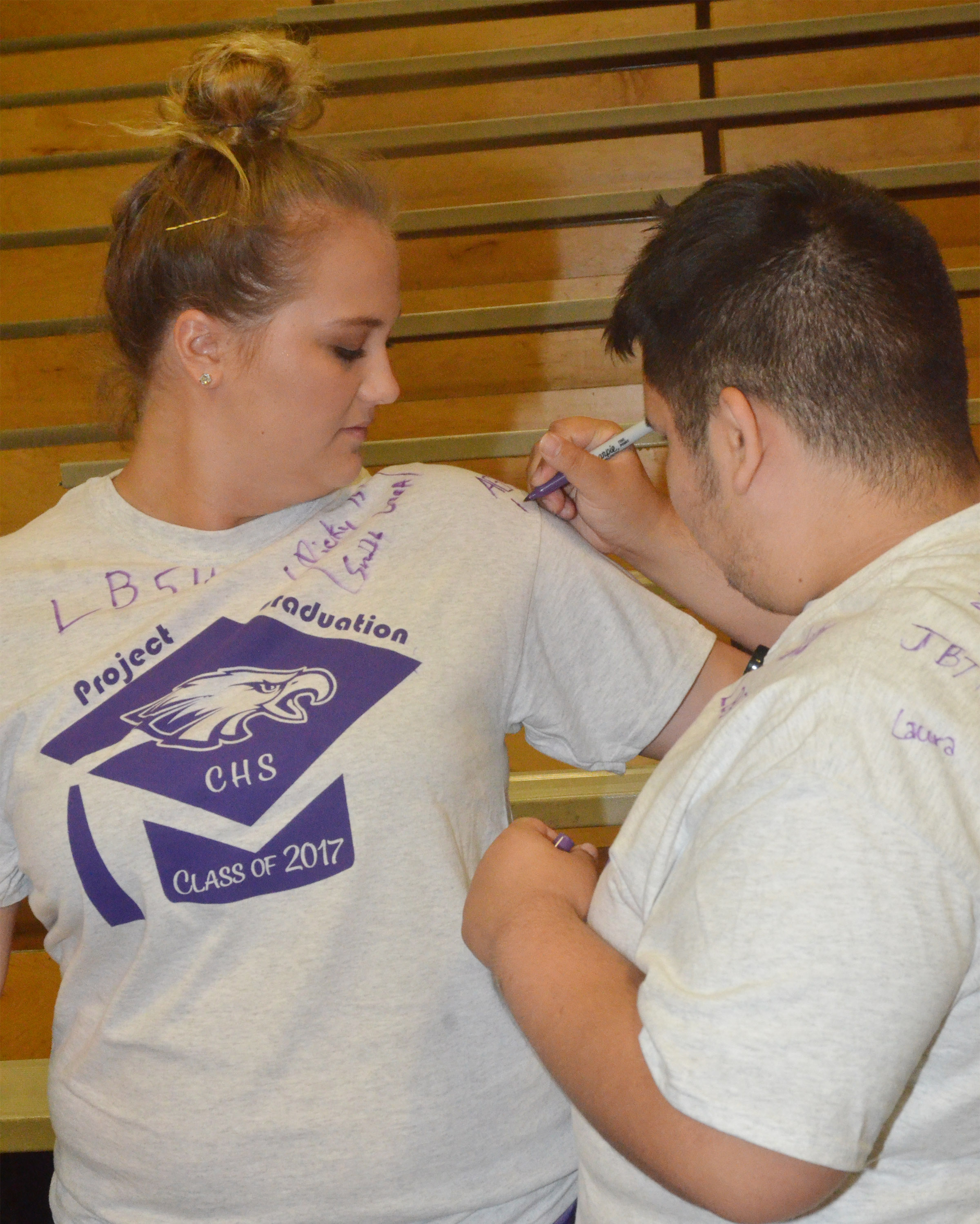 CHS senior Robert Tungate signs Brenna Wethington's project graduation t-shirt.