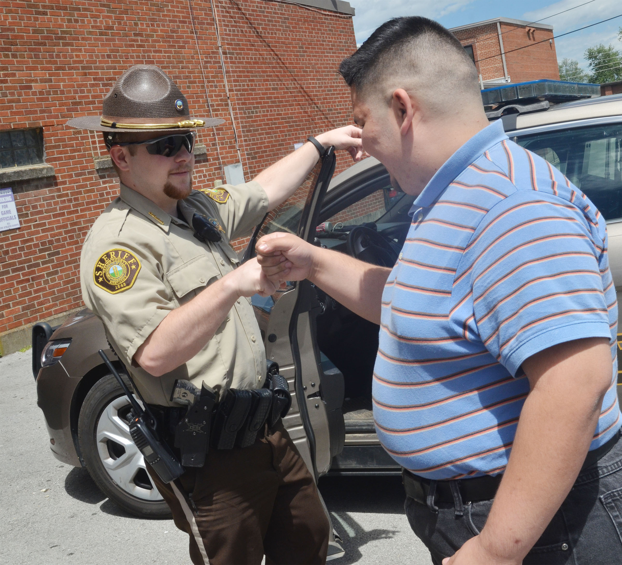 Taylor County Sheriff's Deputy Tyler Finn bumps fists with CHS senior Robert Tungate.