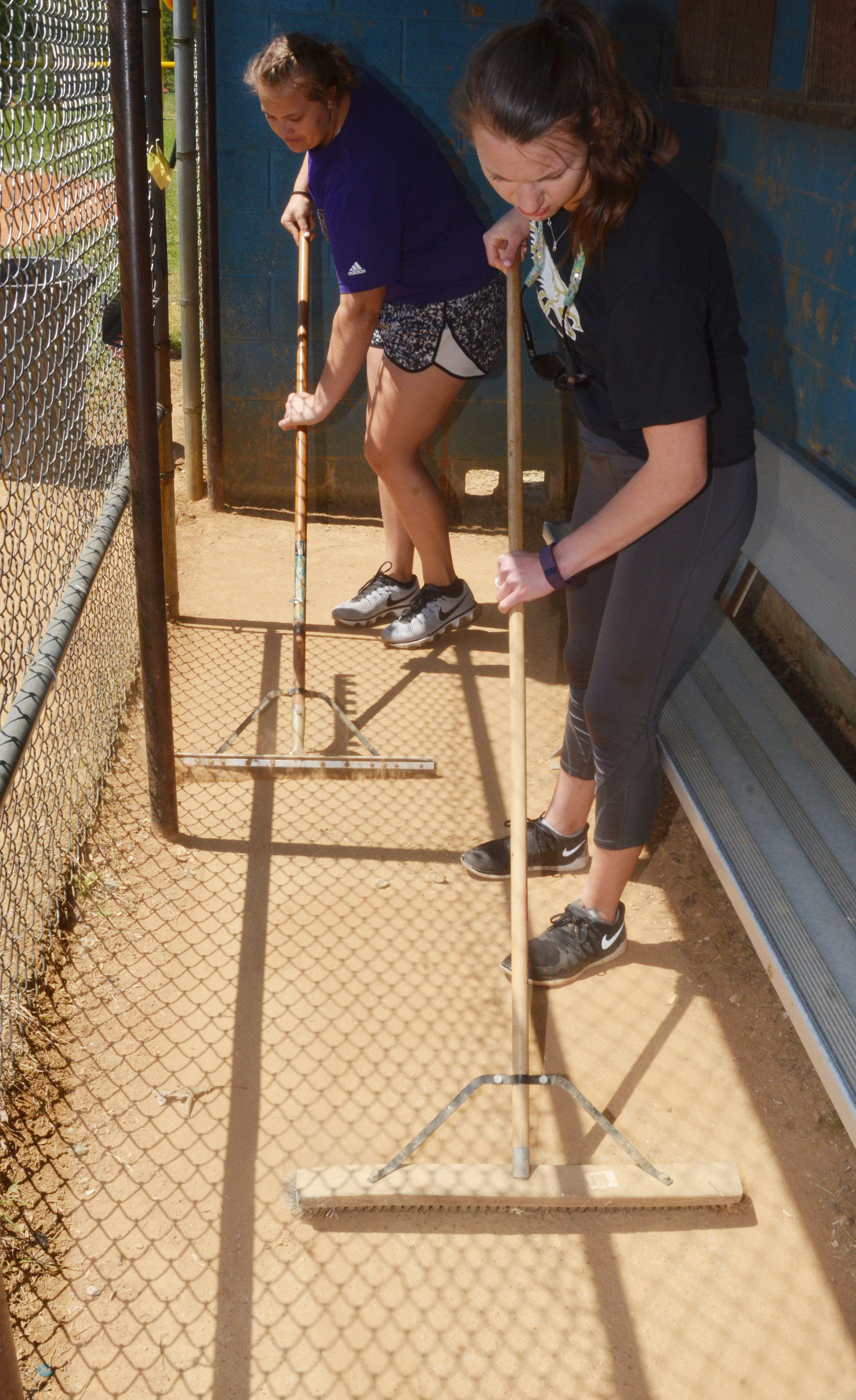 CHS seniors Brenna Wethington, at left, and Caylie Blair sweep the dugouts at Miller Park.