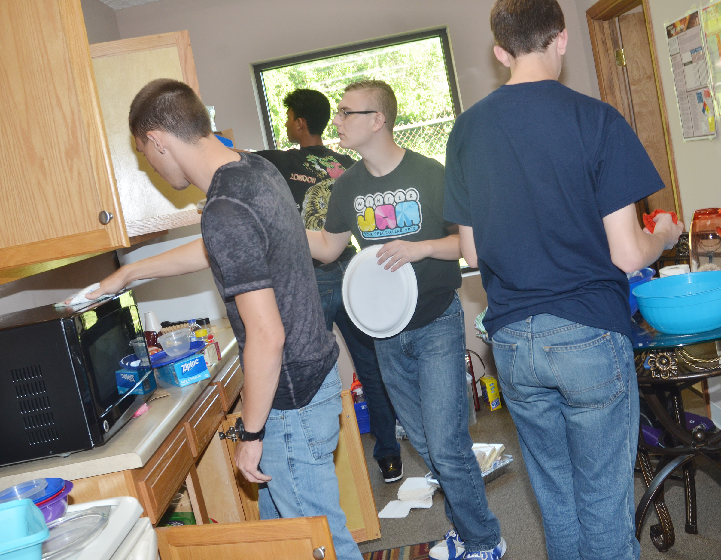 From left, CHS seniors Jordan Pratt, Daniel Silva, Ben Rafferty and Murphy Lamb clean the kitchen at Green River Ministries.