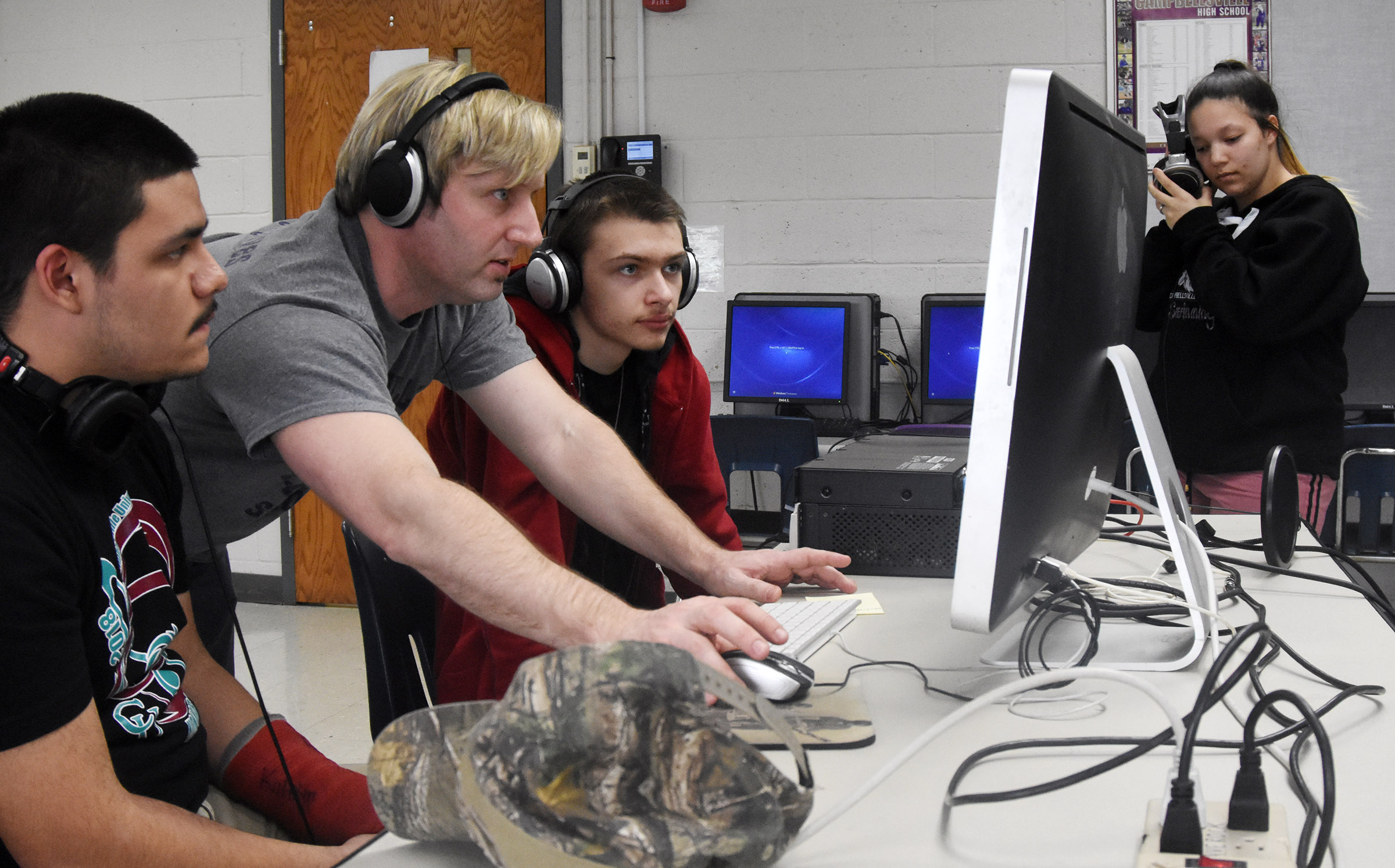 CHS junior Nick Cowan, at left, and sophomore Kris Releford learn to record music with instructional assistant David Williams. At right, freshman Tierra Bridgewater listens to the song she just recorded.