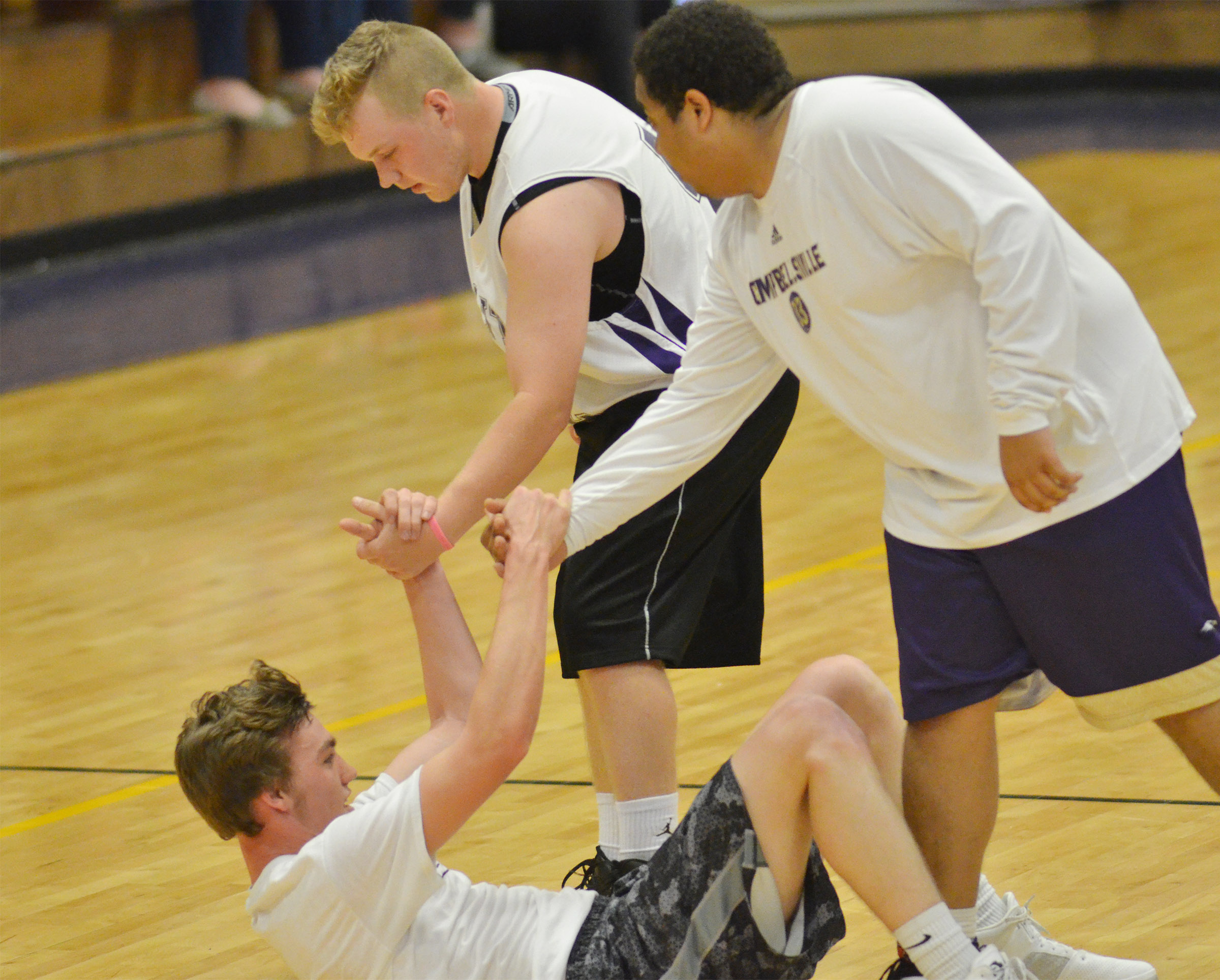 CHS seniors Noah Wagers, at left, and Ricky Smith-Cecil help classmate Zack Bottoms up after a play.