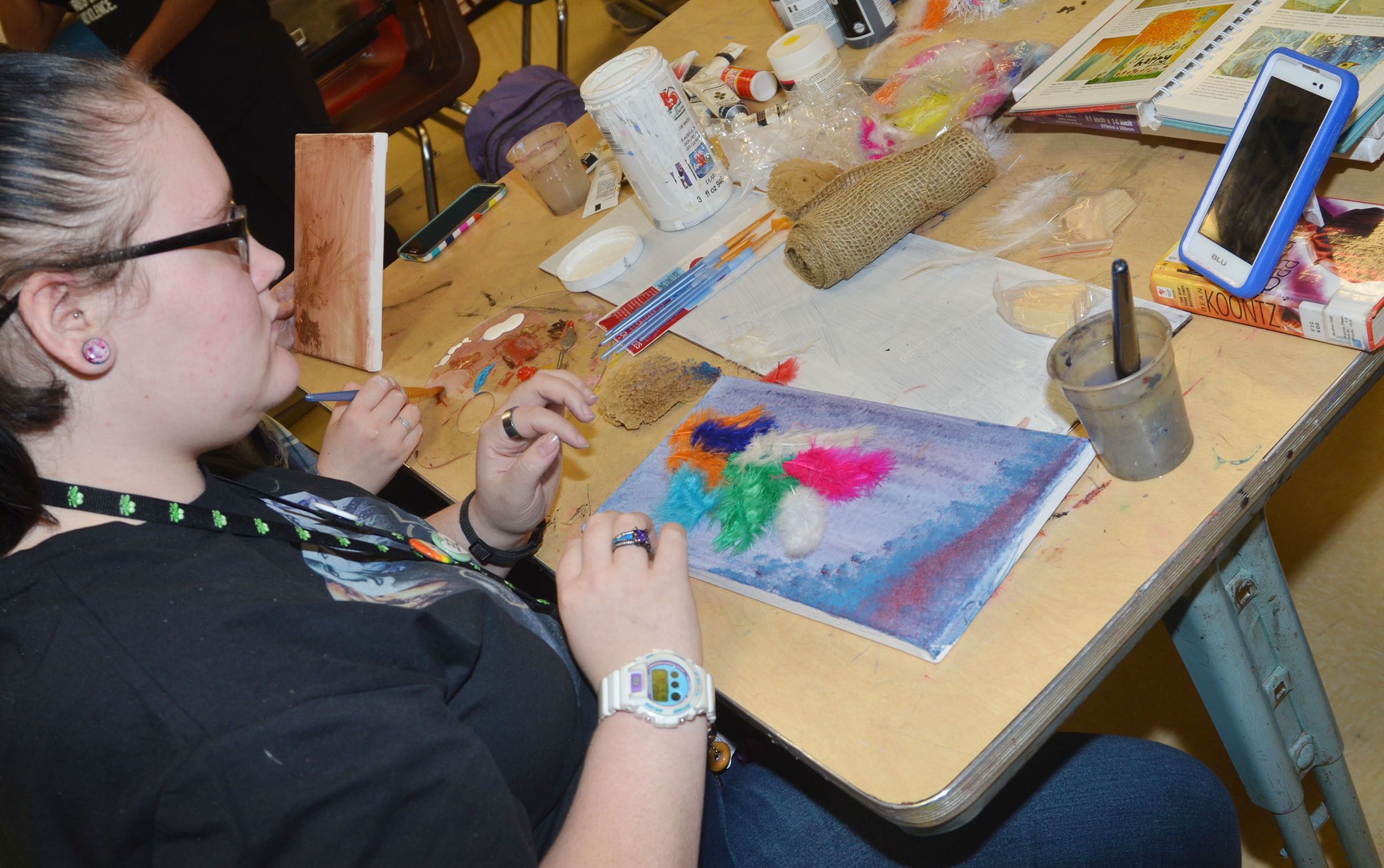 CHS specialized art student Jasmine Cox, a junior, adds feathers to her painting.